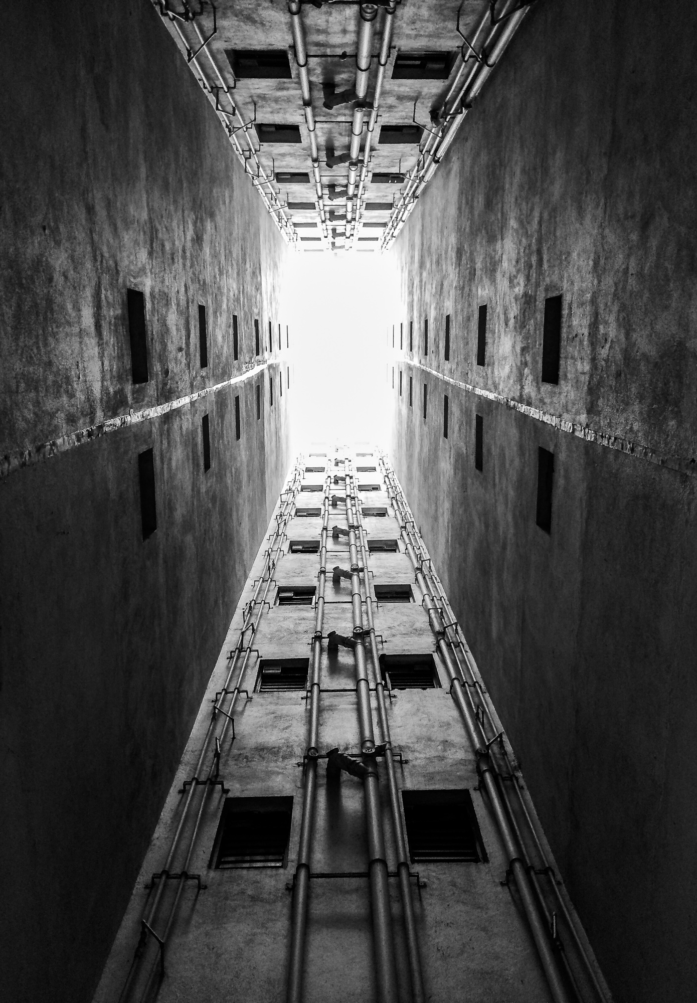 looking up to the neglected area of a high rise resident apartment building where bathroom and service area windows opens.