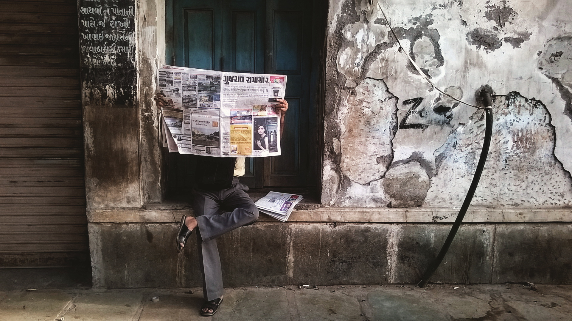 A Common man takes his time out to read news paper in between his time for work while leaving from Home.
