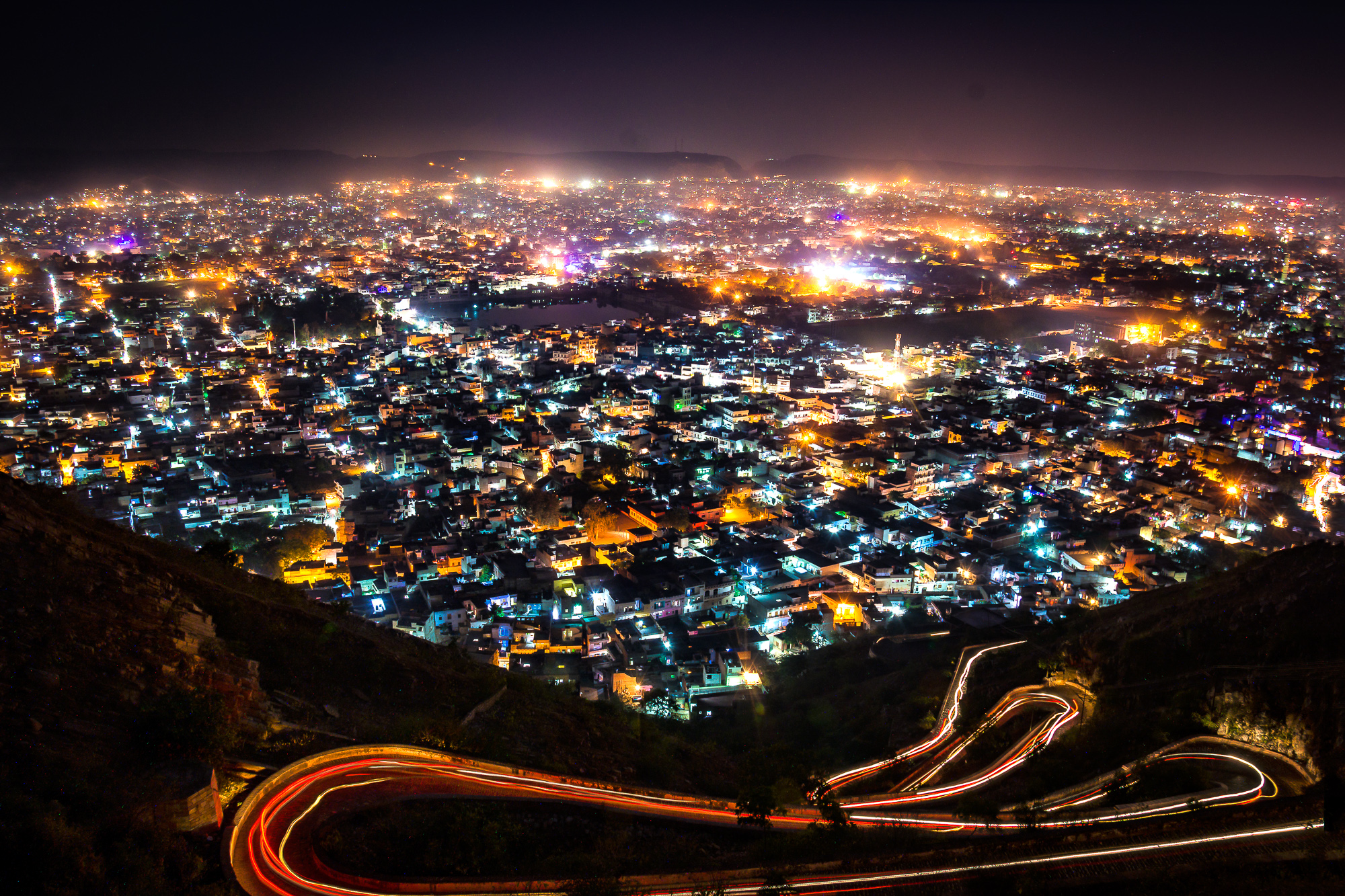 This image is shot from Nahargarh Fort. There is a shortcut road to the fort which can be covered by foot or bikes. But is it too steep for bike as well. As the bikes went down the road tracing the path and the city glittering make me to capture this.