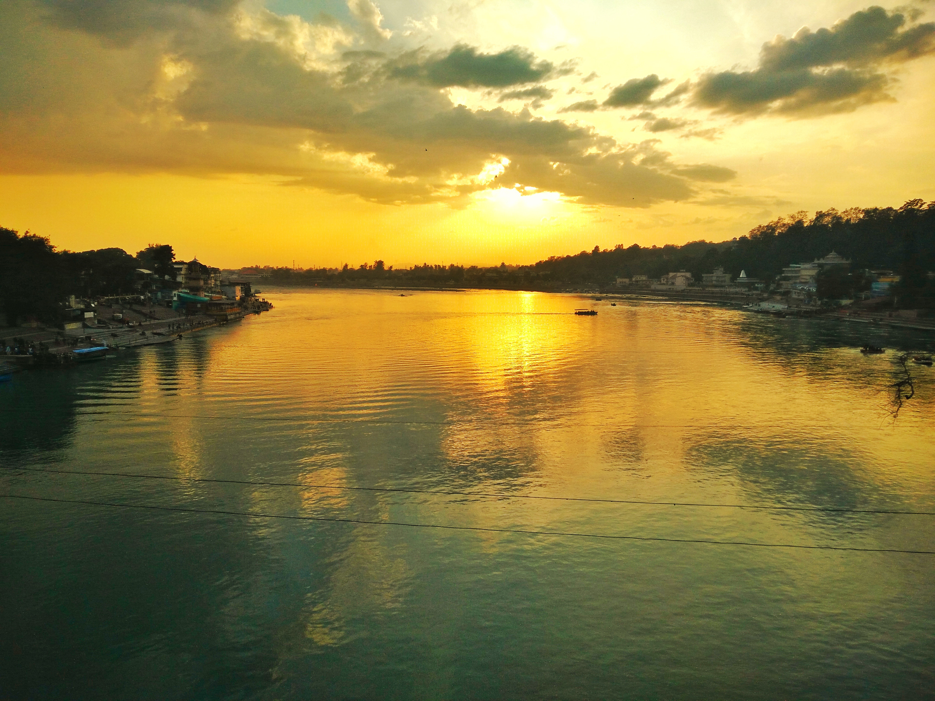 The picture captures a moment of stillness of the ever flowing river Ganga. This holy river is a witness to the days and nights, years and centuries and continues to witness the flow of time. Sitting by the side of this river, experiencing the coolness which the water carries, makes the sight of the sunset even more soothing and relaxing.