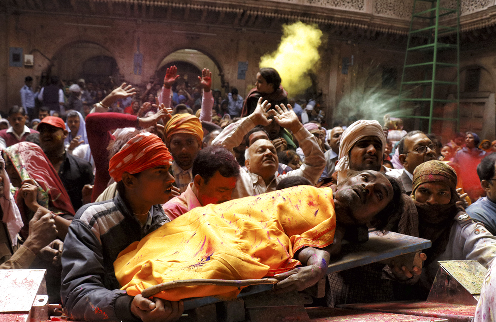 Physical challenged person getting support from his family to celebrate holi festival in banke bihari