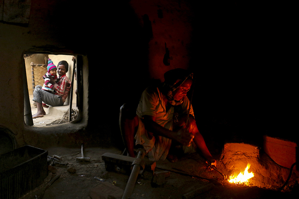 A blacksmith is working for his family.