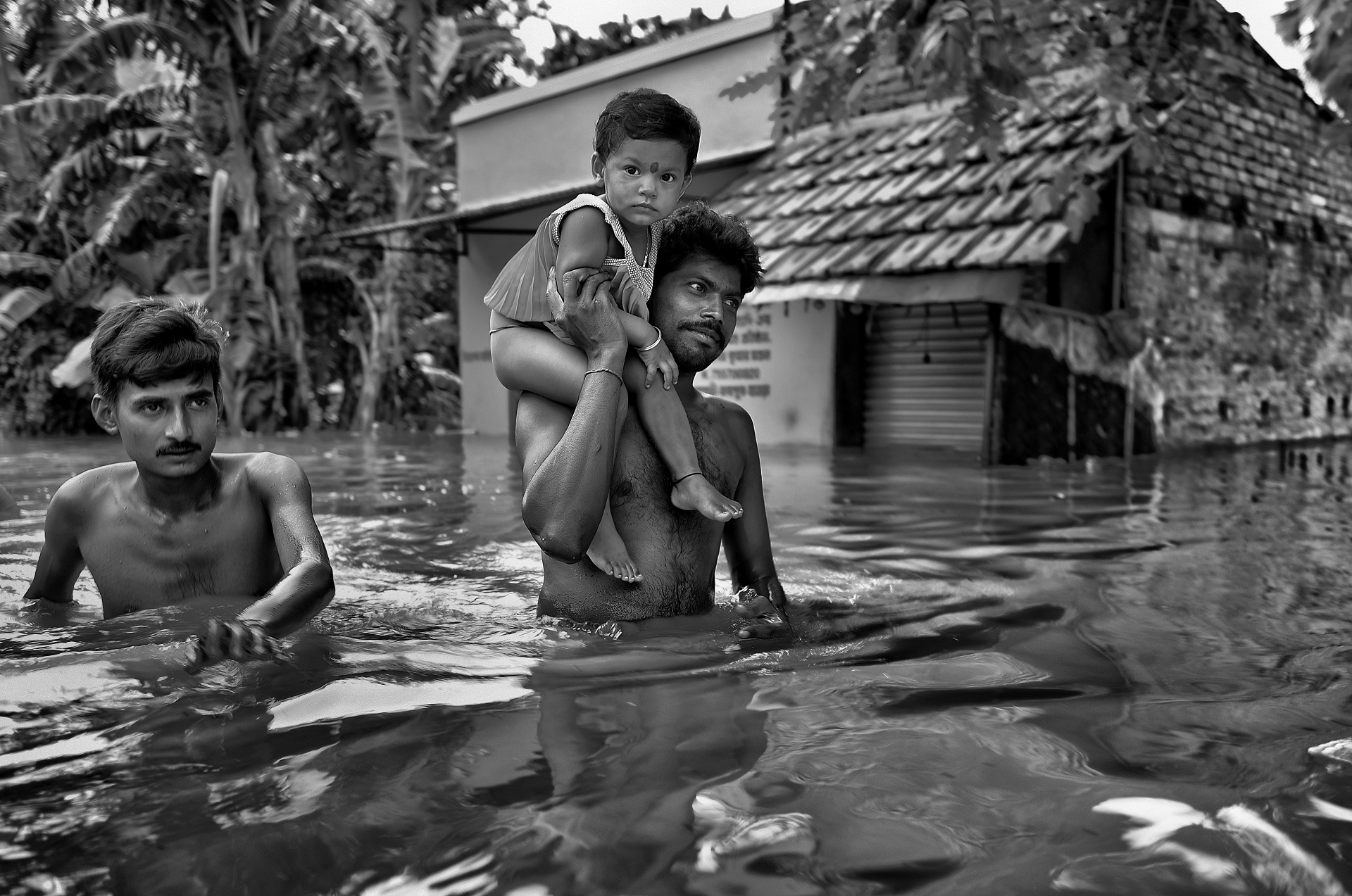 A poor father is coming out from the submerged village of Howrah with his child on shoulder and going to the higher place for survival.