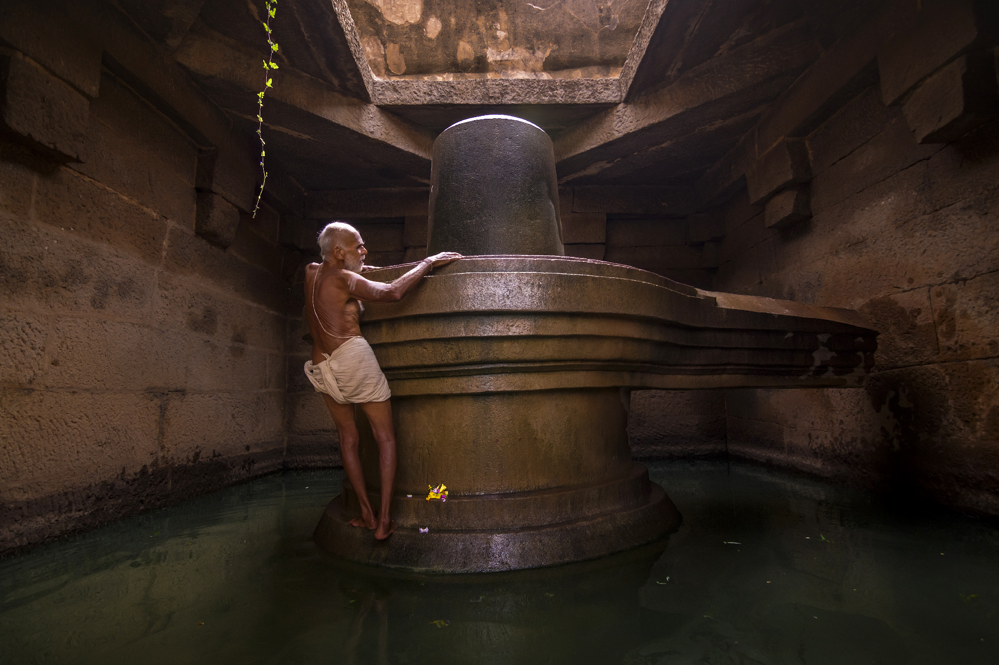 While travelling to hampi I click this beautiful story telling picture in badavilinga temple.  This is the only priest who perform adoration in this temple from last 65 years the priest was 85 years old he cant even walk properly but in the devotion of lord shiva he climbs up cleans the sculpture and worships there.he walk through that opaque water to reach to god and shows his love towards shiva. He presents the true example of love towards his religion & inspire many of us ,   for me its a real inspiration for all.