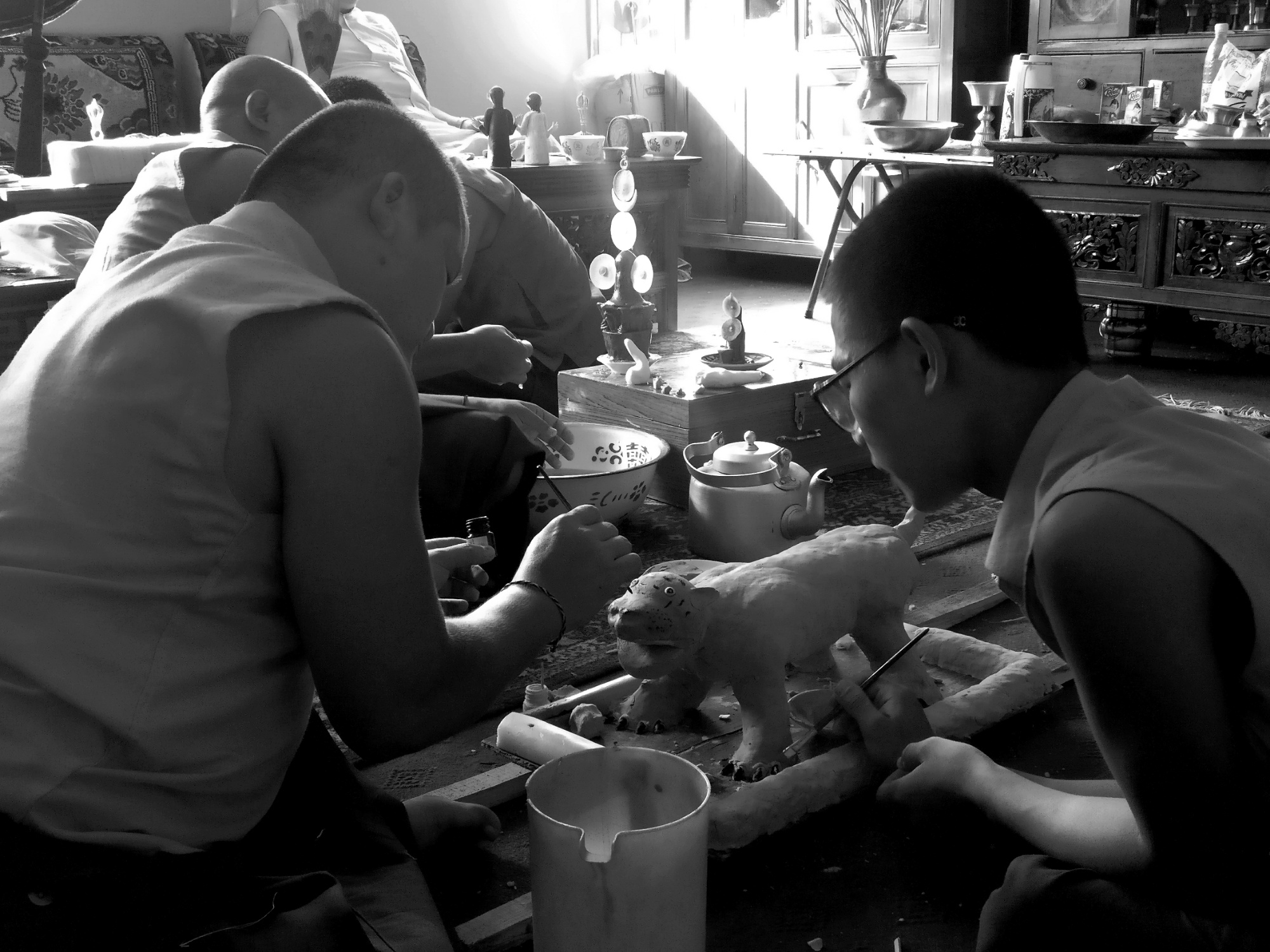 The senior lama (monk) teaching his student the art of painting idols used for rituals.