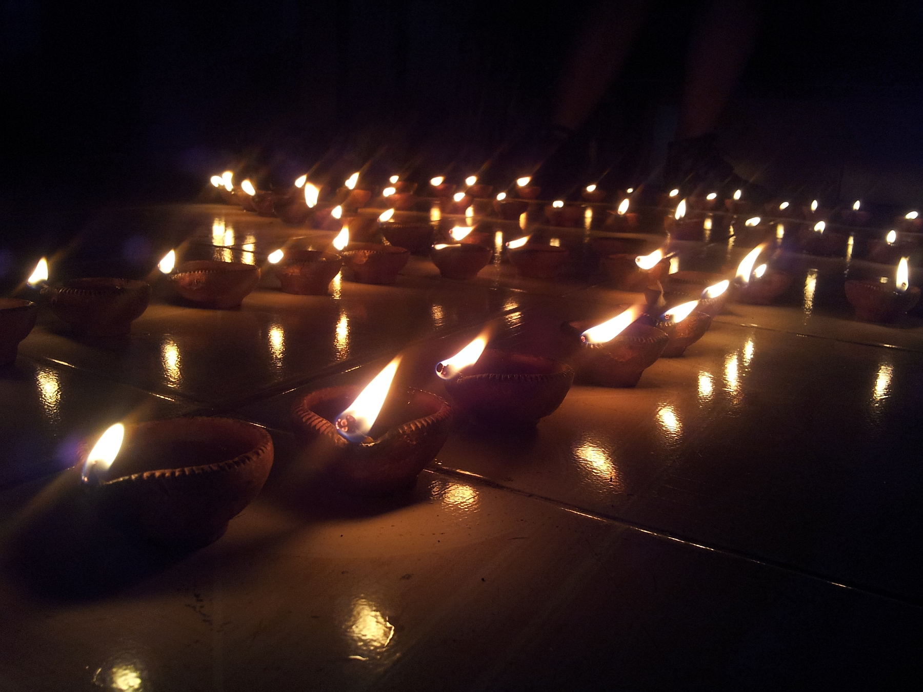 a display of earthen diyas lit up to decorate personal spaces in home ... celebrating the spirit of diwali ...