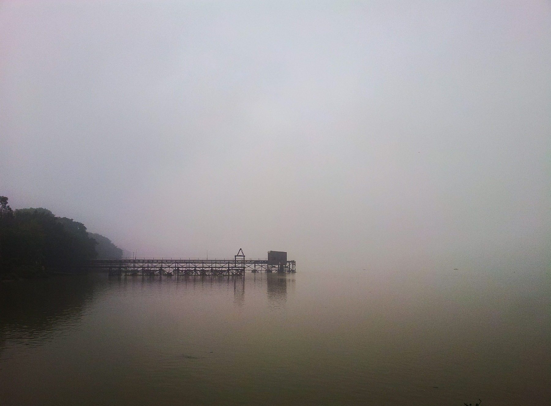 ... the calm waters of the River Hooghly highlight abandoned jetty in the early morning clouded with fog ... heralding the setting in of winters ...