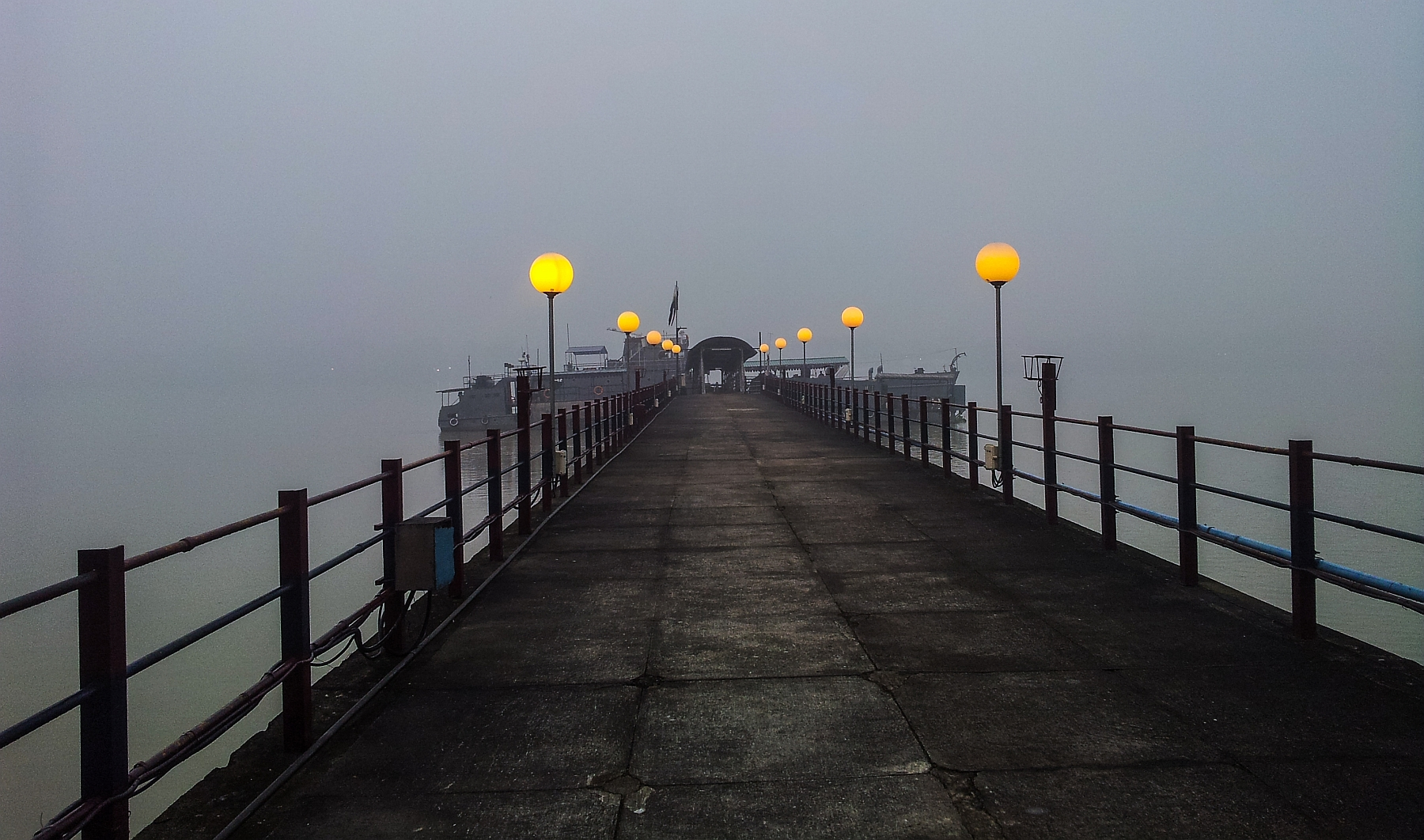 the jetty lights cast a warm ambiance to a dull scene on a early winter morning ...