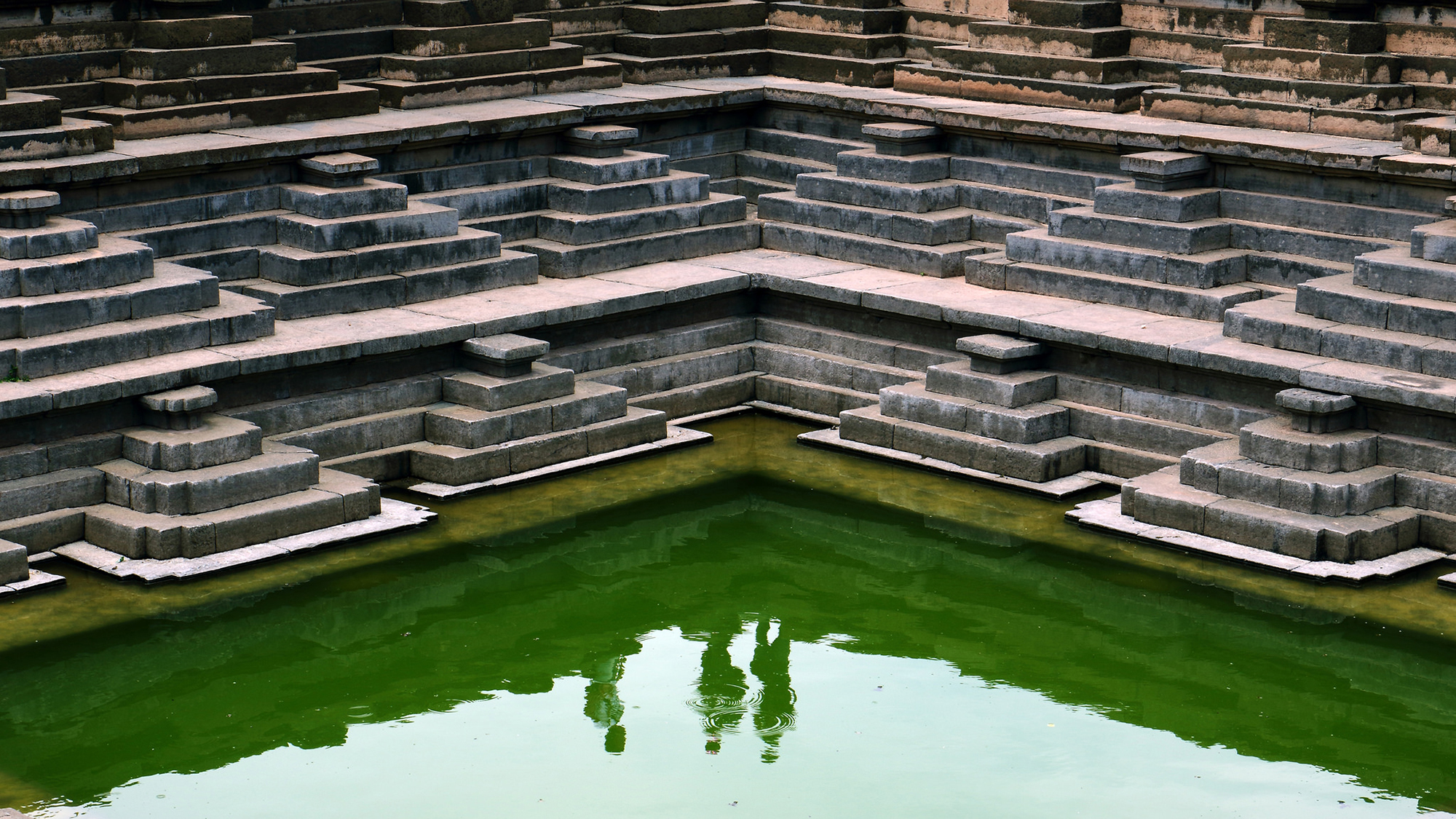 The fascinating patterns and the symmetry of the Pushkarni stepwell in Hampi where each level was carved in a repetitive triangular shape was very alluring. The three corners of the pyramid shaped stairs, the three dimensional angle where two flanks of the tank meets and the three tourists shadows on the water below presented a magical frame.