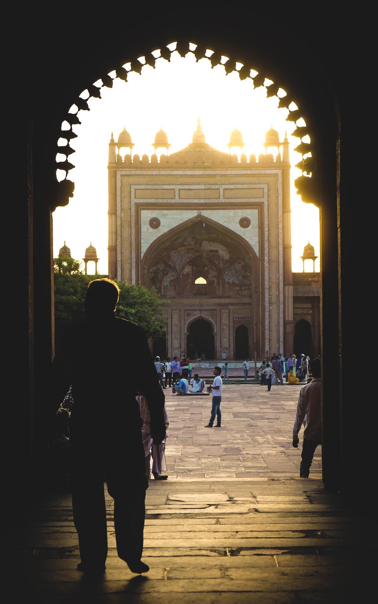 Shot inside the buland darwaza premises, A famous historical place of worship. A man enters the gates as the sun shines behind the opposite gate. A gleamy mood.