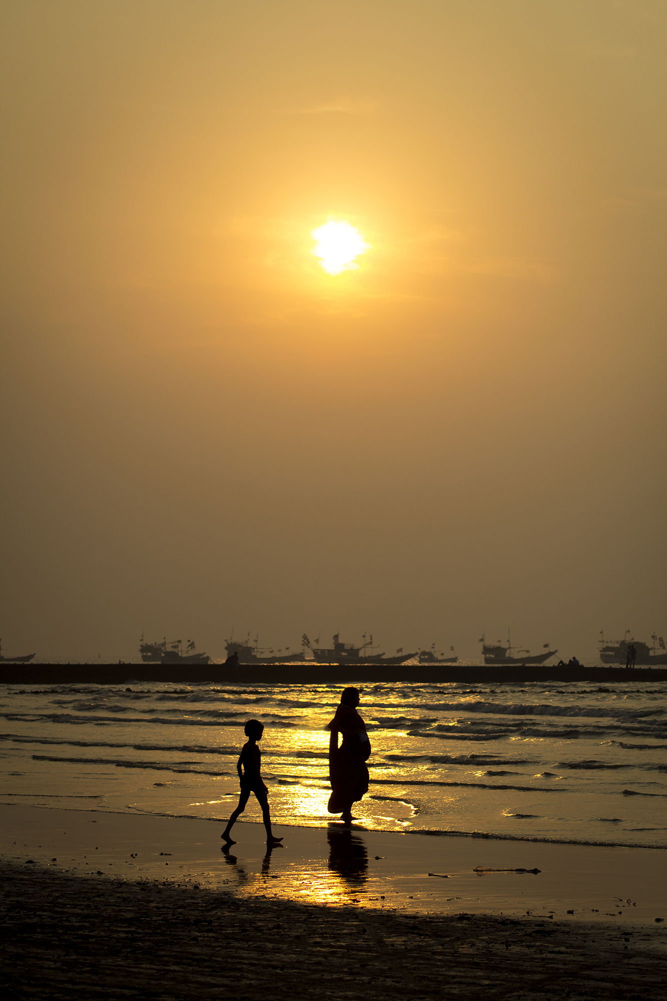 This image was taken at Gorai Beach - Mumbai. I was just roaming around and saw this kid with his mother opposite to the sun giving this nice silhouette effect.