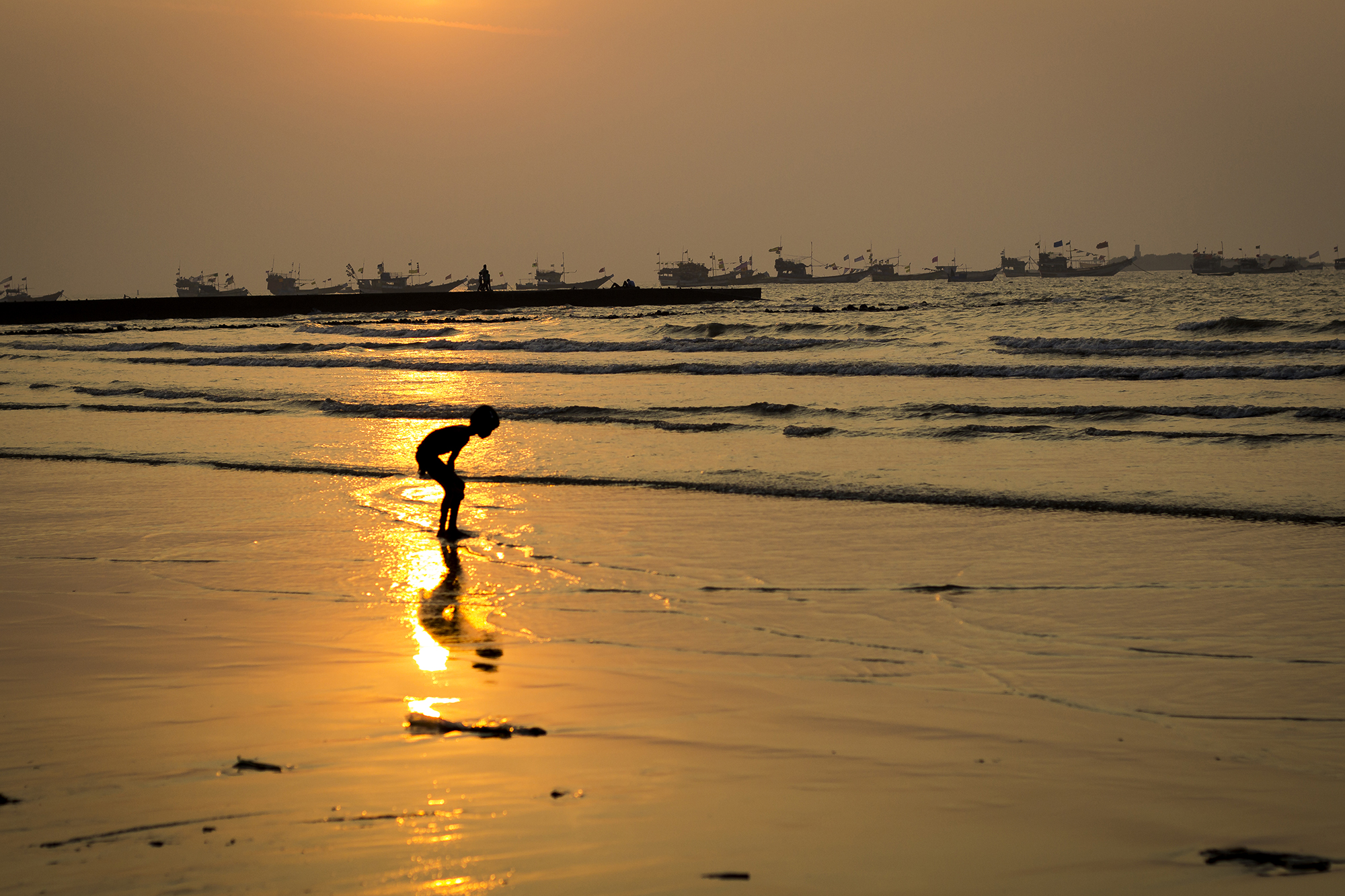 This image was taken at Gorai Beach - Mumbai. I was just roaming around and saw this kid playing in sea searching for some shells in the sand. He was opposite to the sun giving this nice silhouette effect.