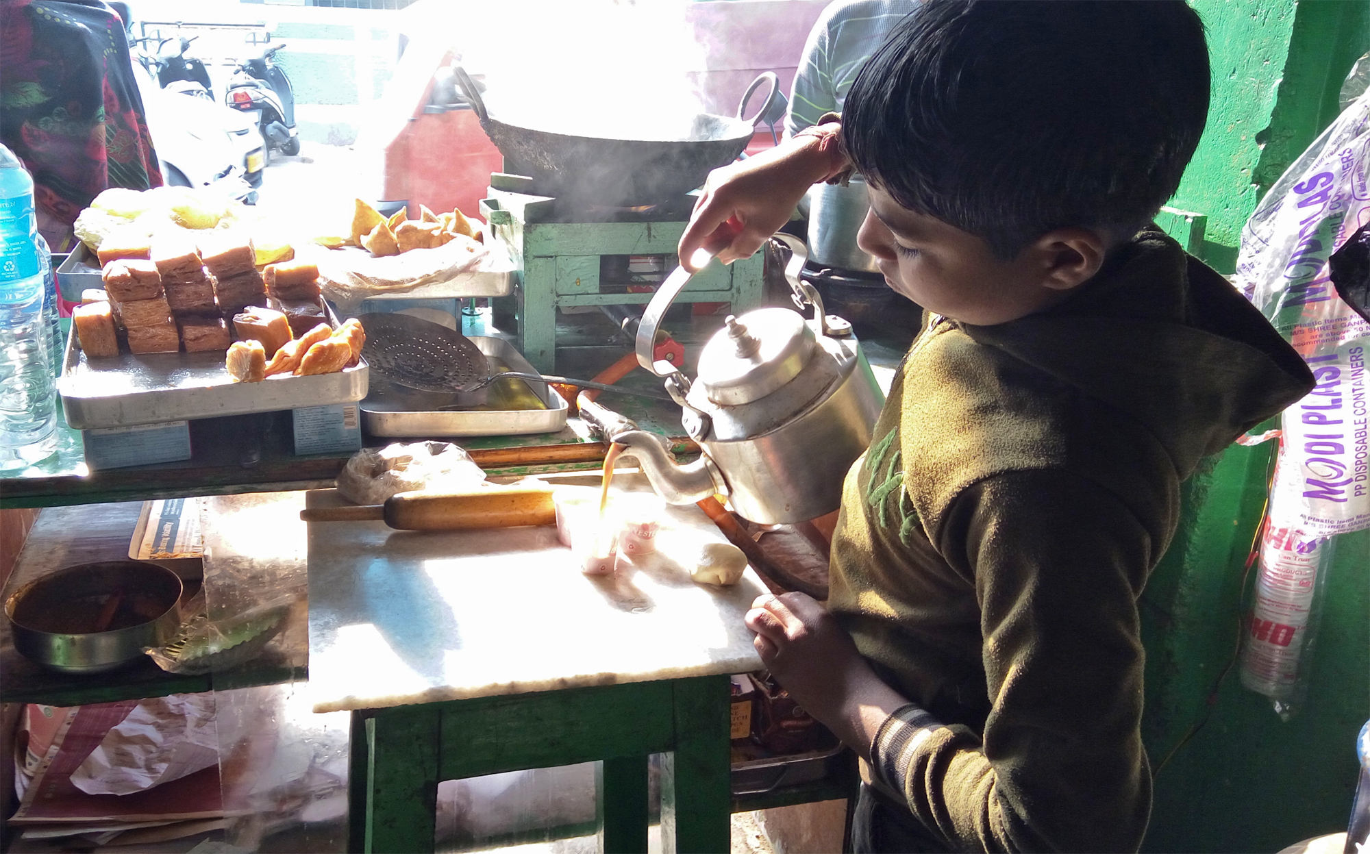 A boy is pouring Tea in tea containers to earn for him and his family.