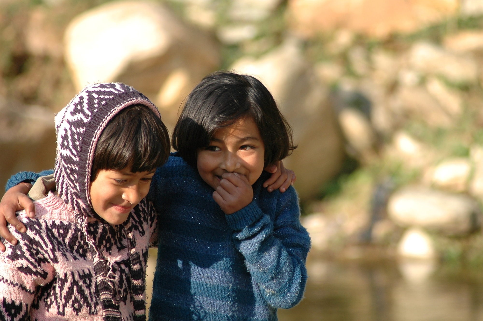 Two little girls share a secret (or a joke) while crossing a stream in Ramgarh village, Uttarakhand.