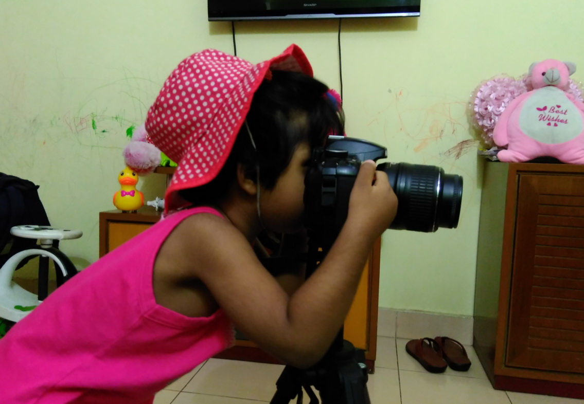 Little girl experimenting with camera in home