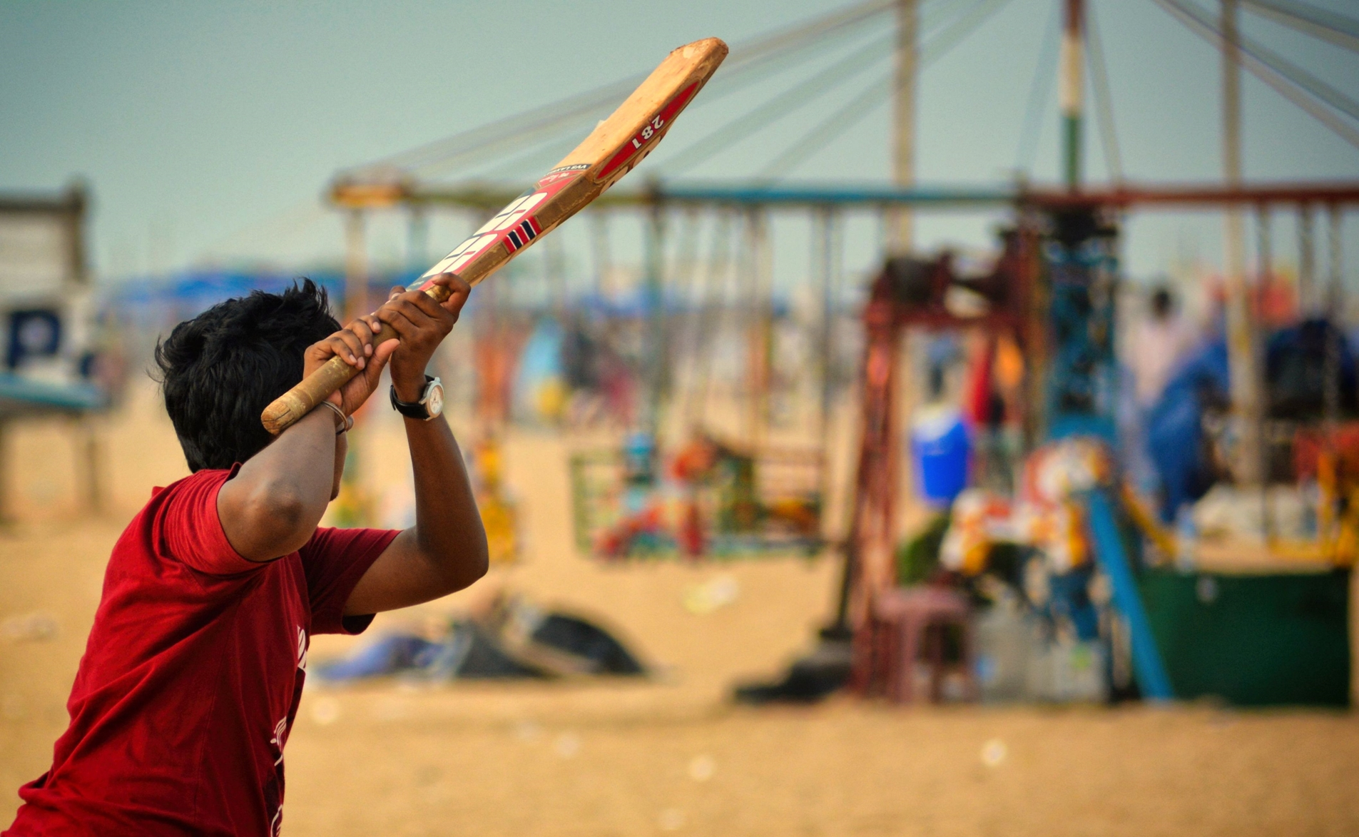 This picture showcases a teenager enjoying his summer by playing beach cricket