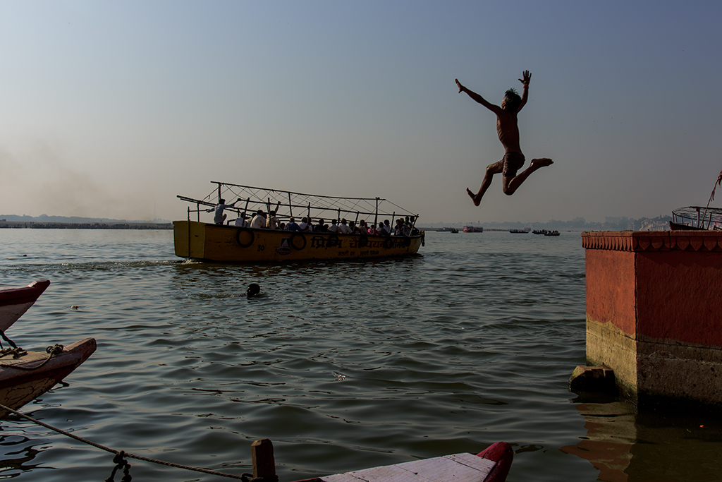 A boy jump in to the Ganges river.