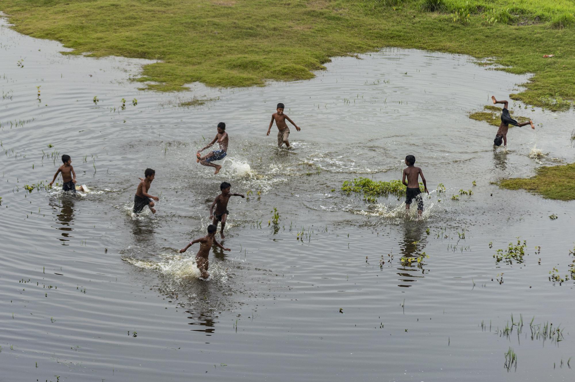 Children enjoying their bath in a hot summer day, near Barasat, Kolkata