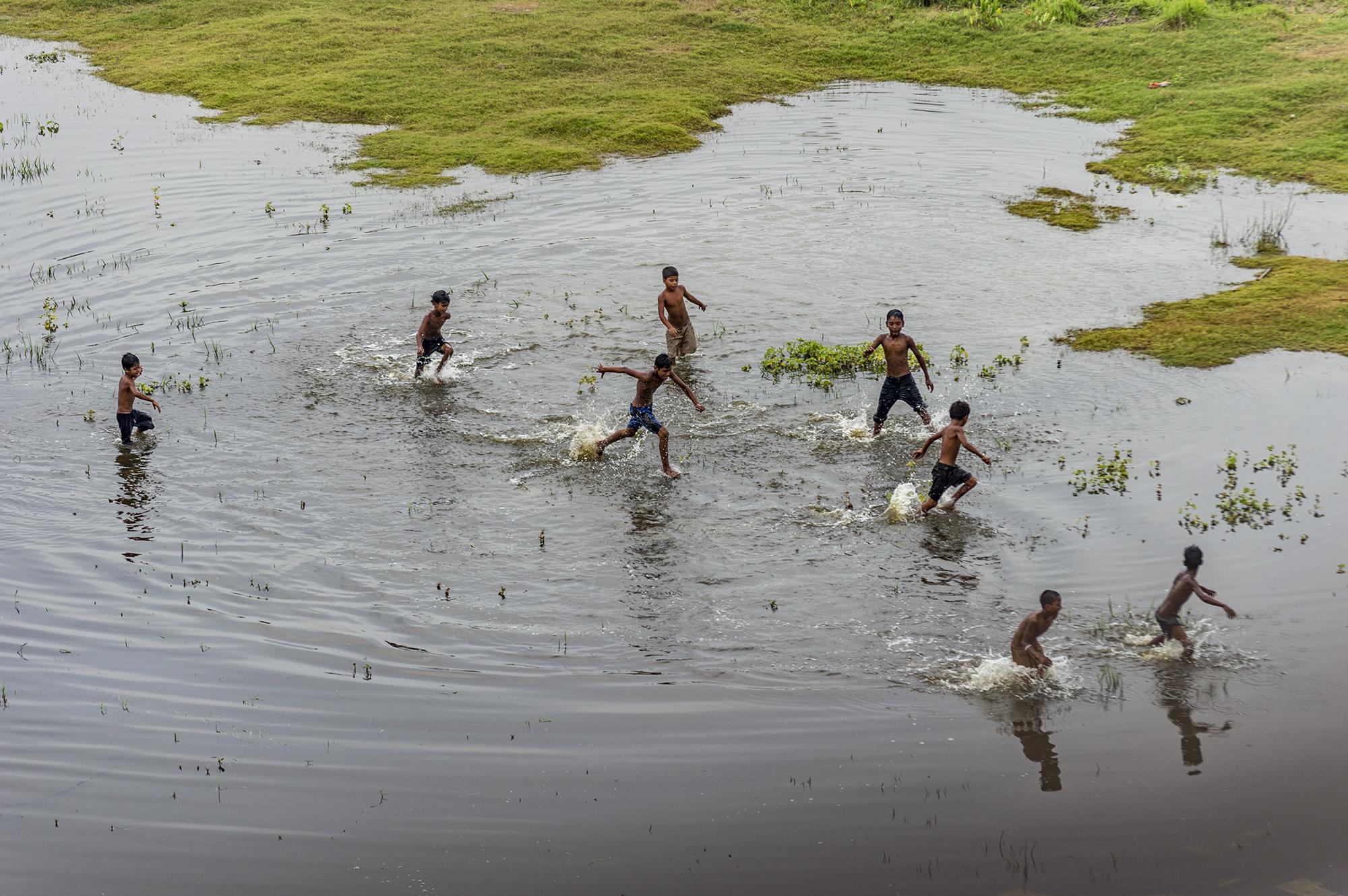Children enjoying their bath in a hot summer day near Kolkata.
