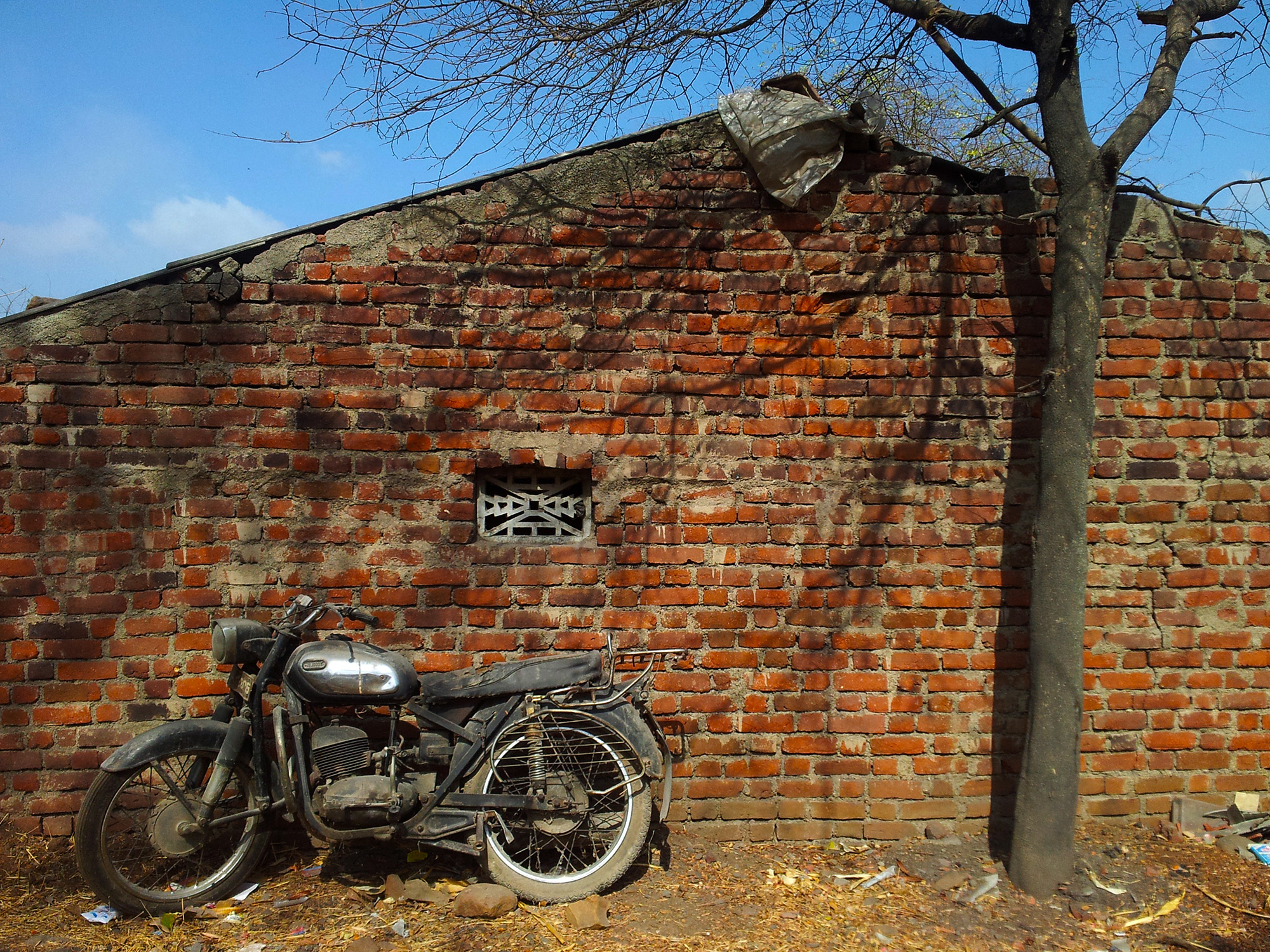 The old motor bike against the red brick wall and the dead tree instantly attracted me to capture all of them in a frame.All the components in the frame has a sense of
