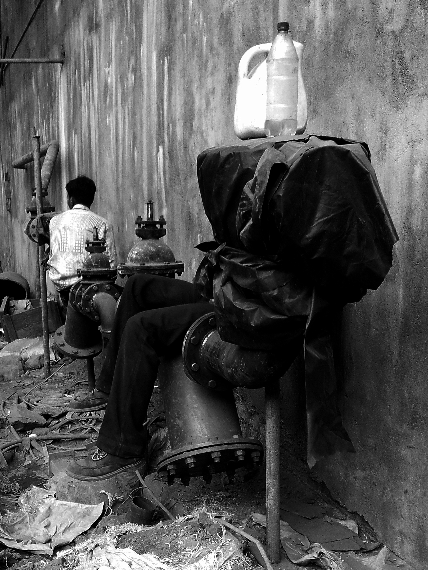 This shot was taken at a under maintenance building.These people were taking rest during the lunch break.I could notice the bottle and the empty container at the head level of the guy which up to some extent symbolises the idleness of mind