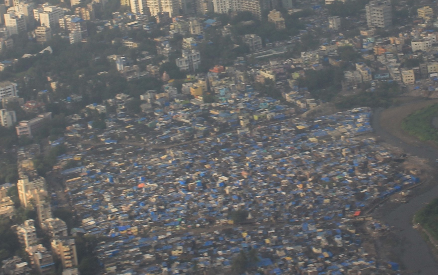 Aerial View of Slums competing for space with affluent highrises disturbing the natural waterways leading water flow to the ocean and precious mangroves