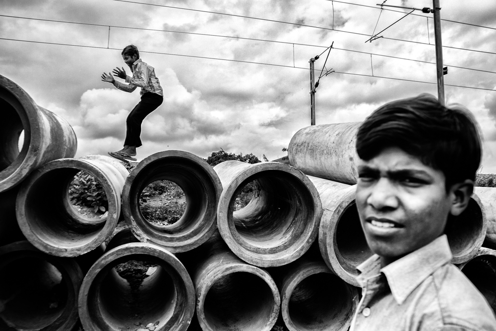 It has been a common problem in India. The work stopped by the municipality led the sewer pipes on the floor and kid couldnt help jumping on them.