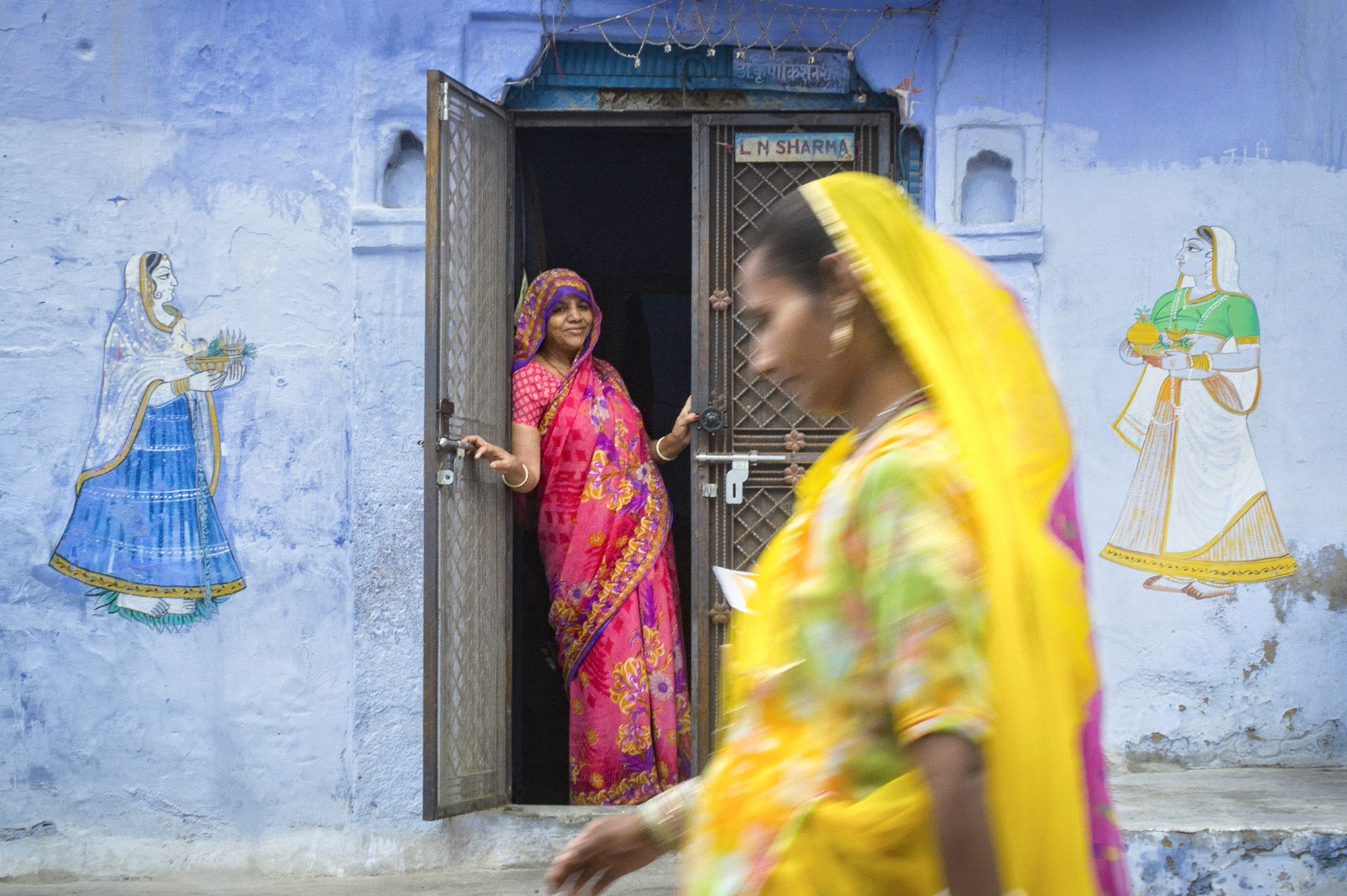 We were on Photowalk around the most famous blue houses of Blue City ,Jodhpur. Saw this house with beautiful art work . I sat in front of her house & clicked couple of shots of the whole lane. In the last decided to take some shots of her. She gently smiled & all of sudden a lady in yellow attire came into the frame. This frame gives us the feel of feminism with joy , pride & also shows the fast life