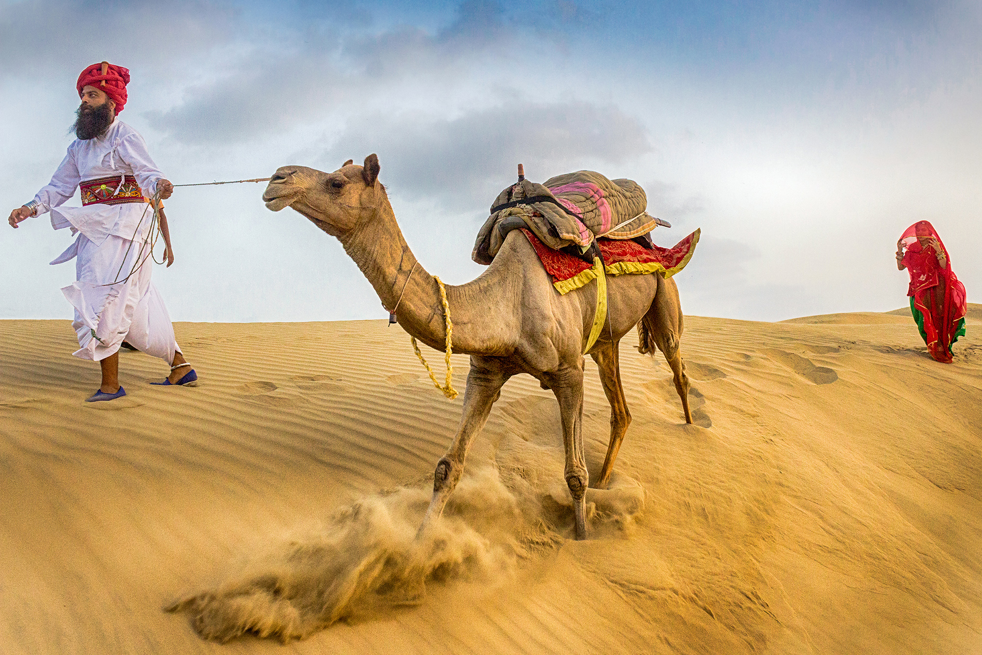 Its a decisive moment. They were coming to our side & all of the sudden camel came to the edge of sand dune. At that end the dune wasn't firm enough & camel tried to keep its grip on that too. Camel slipped a little & that movement is here.