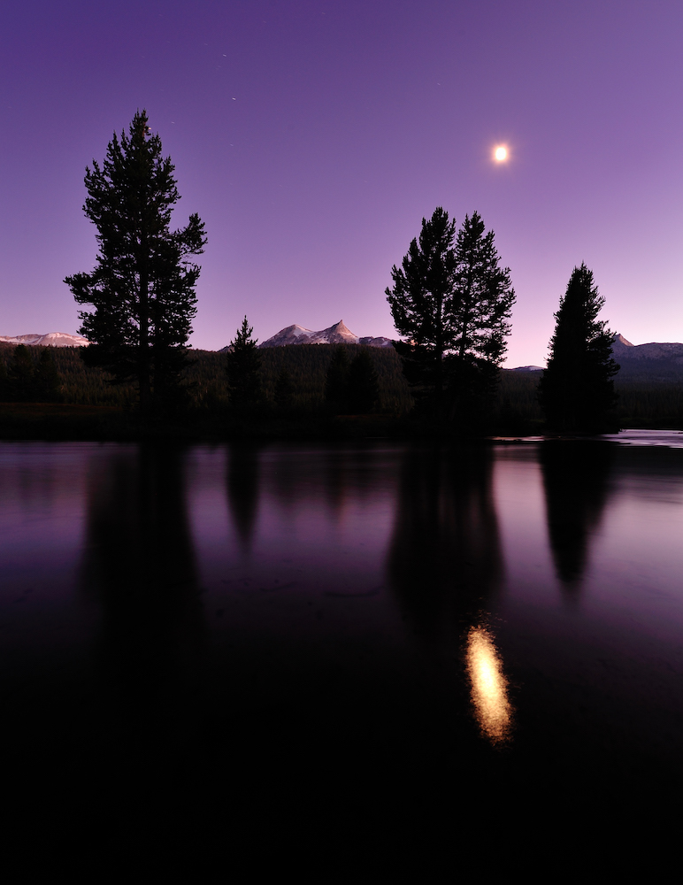 The moon's reflection in Tuolumne River at Yosemite National Park in California, USA, adds to the serene ambience of the landscape.