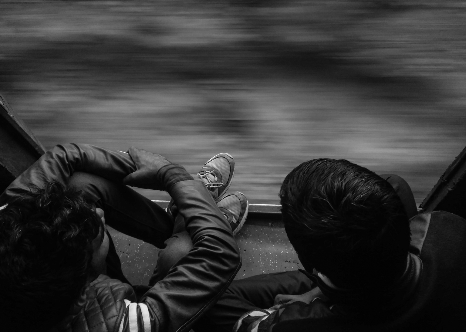 Two boys are sitting just before the door in a moving train.