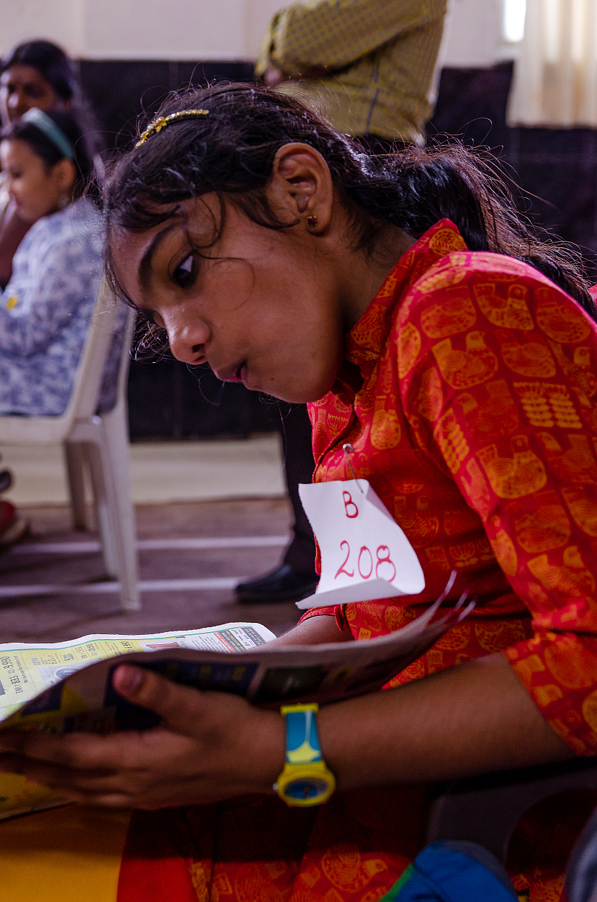 the young girl, a participant in one of the competitions recently held in matunga is waiting for her turn to be anounced. however, she seems lost in the print matter. Unaware of the surrounding the girl is expressive about something interesting in the print.