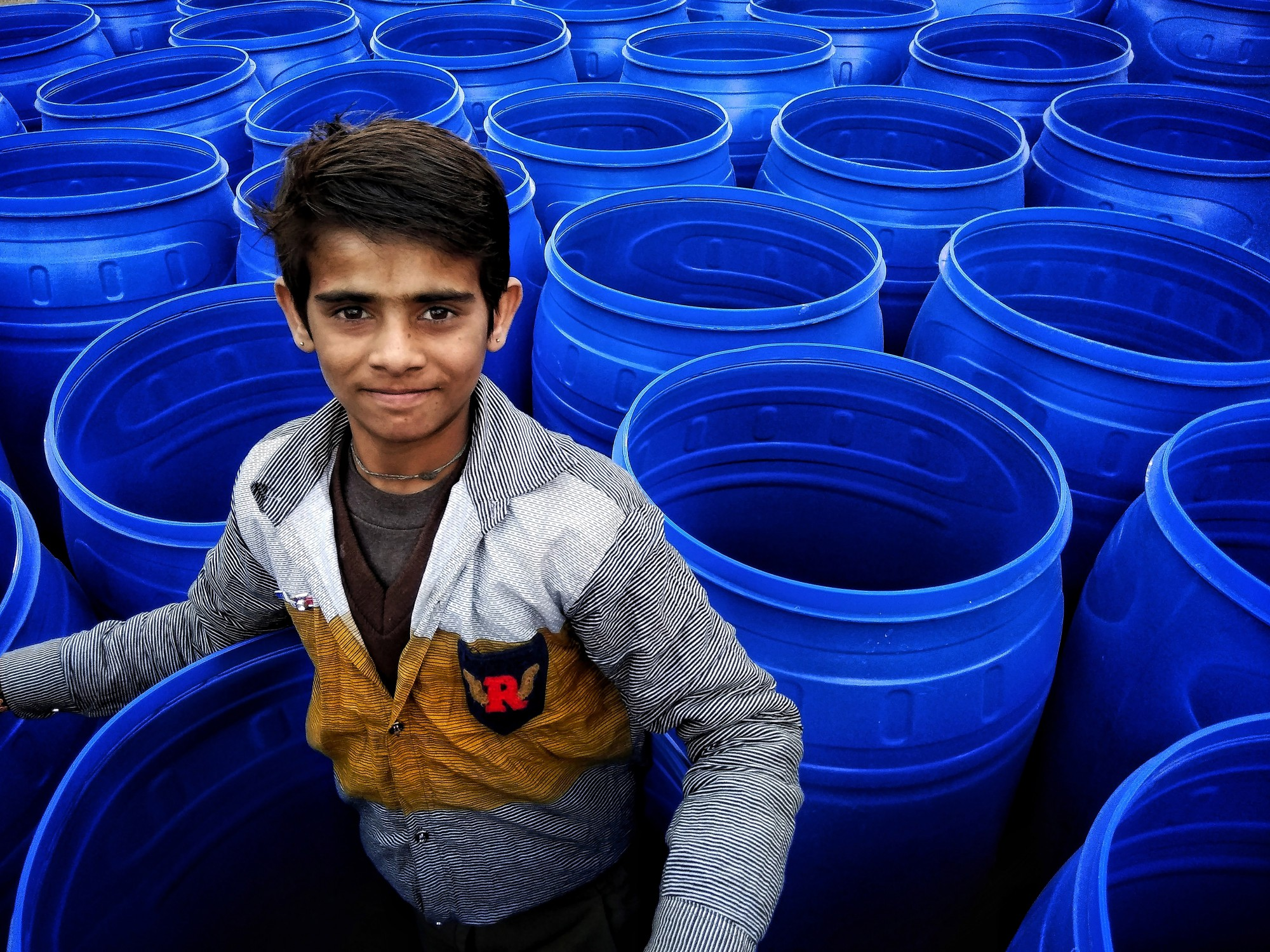 Every year, thousands of pilgrims and families travel to Gangasagar each year to take a dip in the holy water of the river Ganga. Numerous arrangements have been made by the authorities like transit camps for people to stay and take shelter. Here the young boy was found amidst the blue water drums,while his family was busy with the tradional rituals.