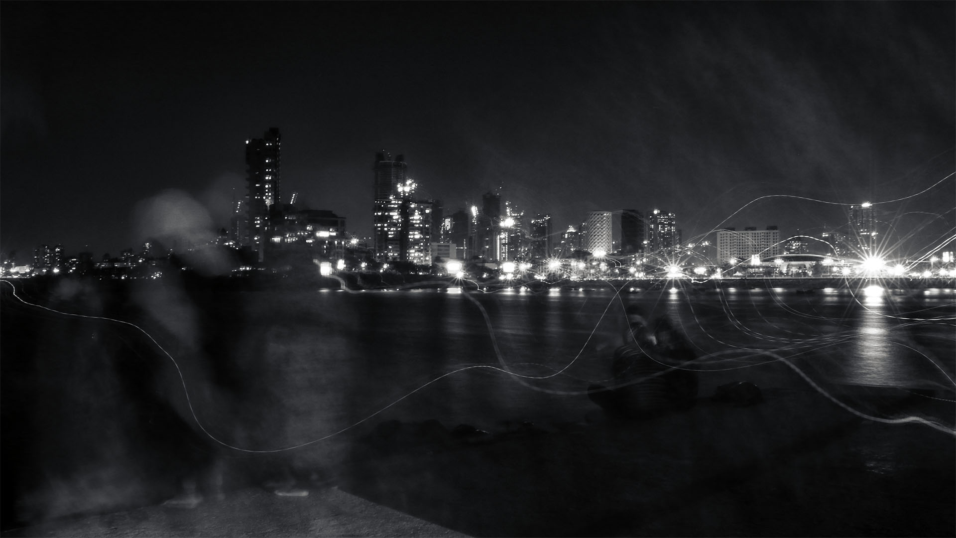 Mumbai was bustling with activity and shone its bright lights as if to call people towards it. Some tourists took pictures of the bright city lights. But the call of the city was strong. So they hurriedly went away leaving a trail of their mobile phone's lights and a shadow of their presence on the banks of the sea on the other side.