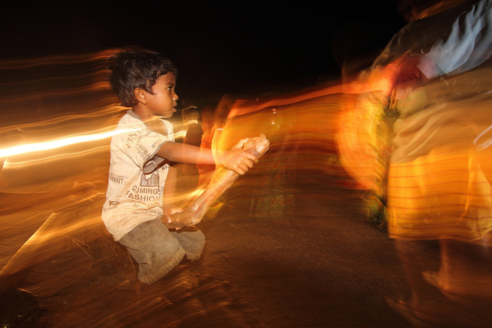 Santal dance form is the signature of purulia.Besides the festival the artists perform for the tourists.Our team was enjoying the vibe and some of us wandering around the crowd. I found the kid on the broken stem,watching the performance.To give a different effect without post processing I used flash in slow shutter speed.