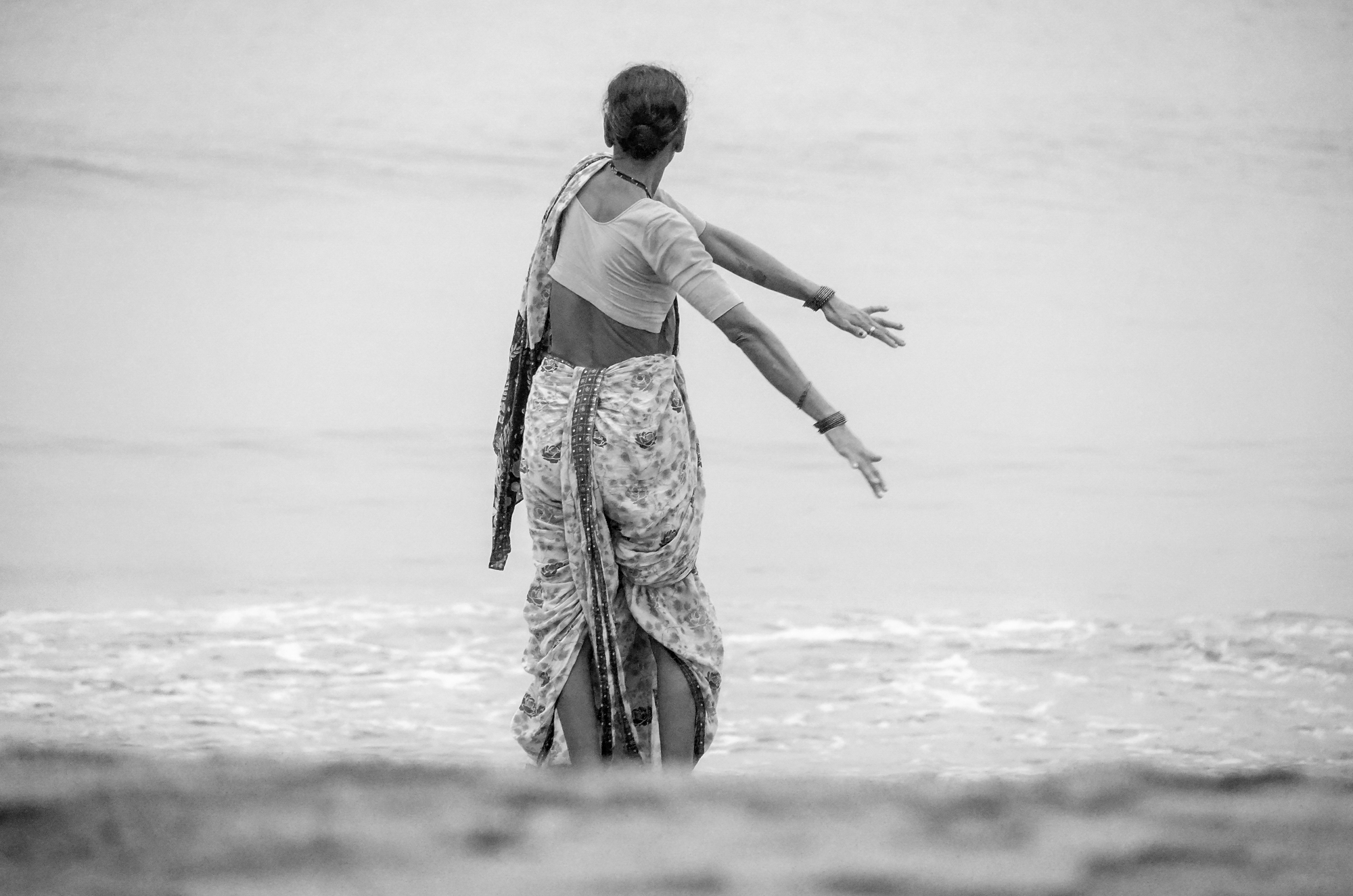 an old lady at versova beach stretching in the early hours