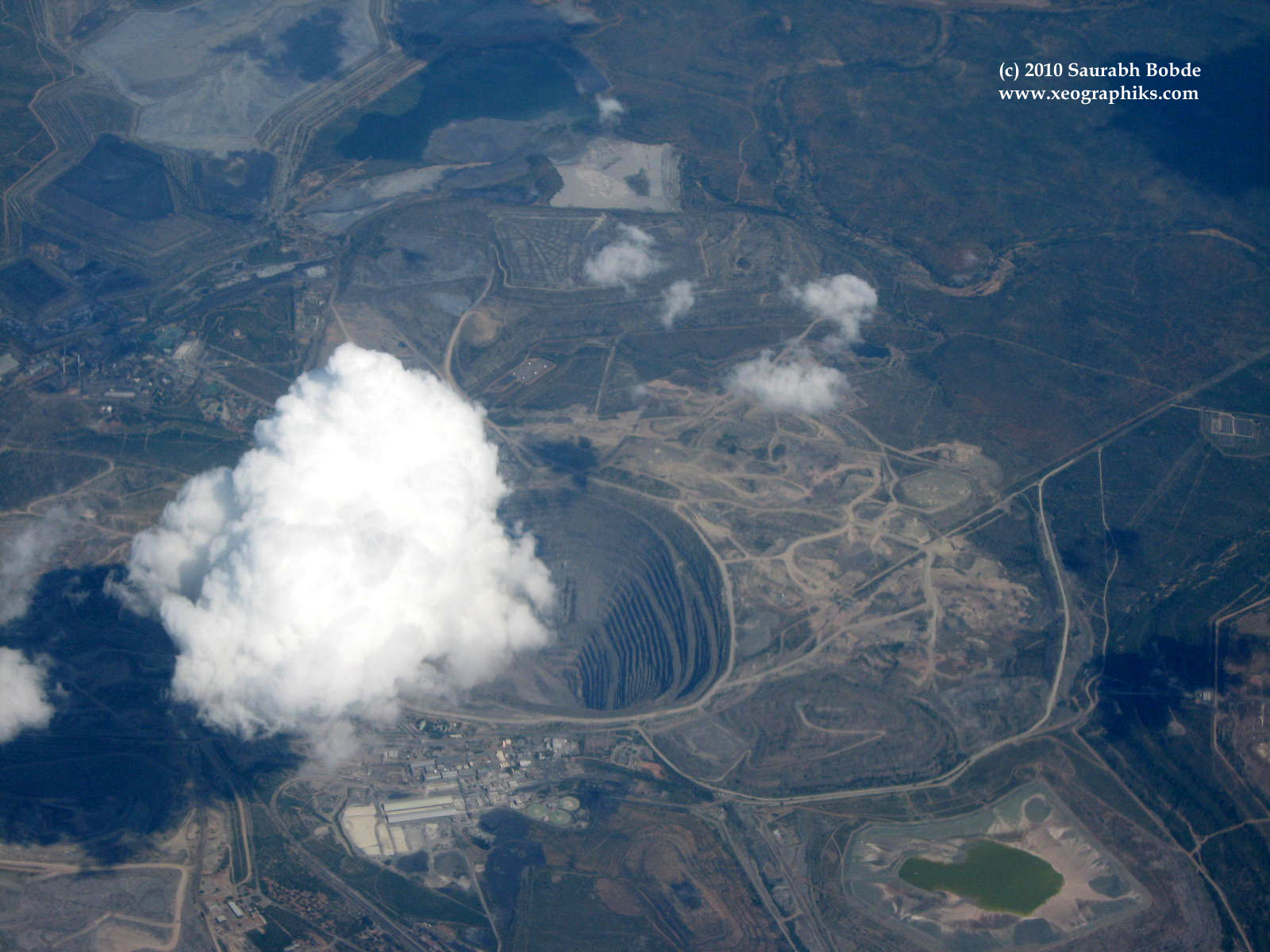 An aerial view (from an airplane) of a cloud appearing to float into a large mine to fill it all up!
