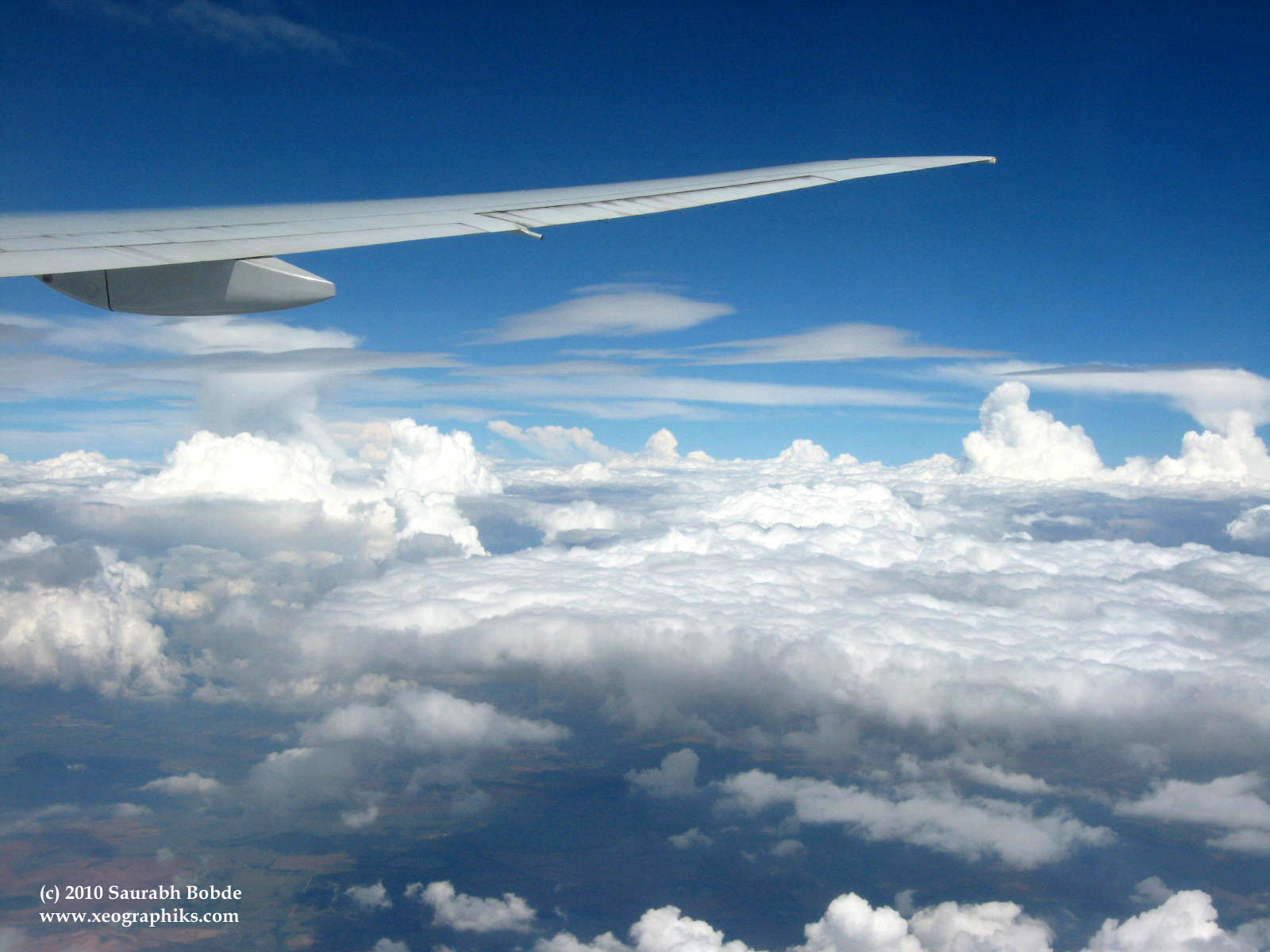 A picture perfect view of blue skies and fluffy white cotton clouds, looking out the window on a flight.