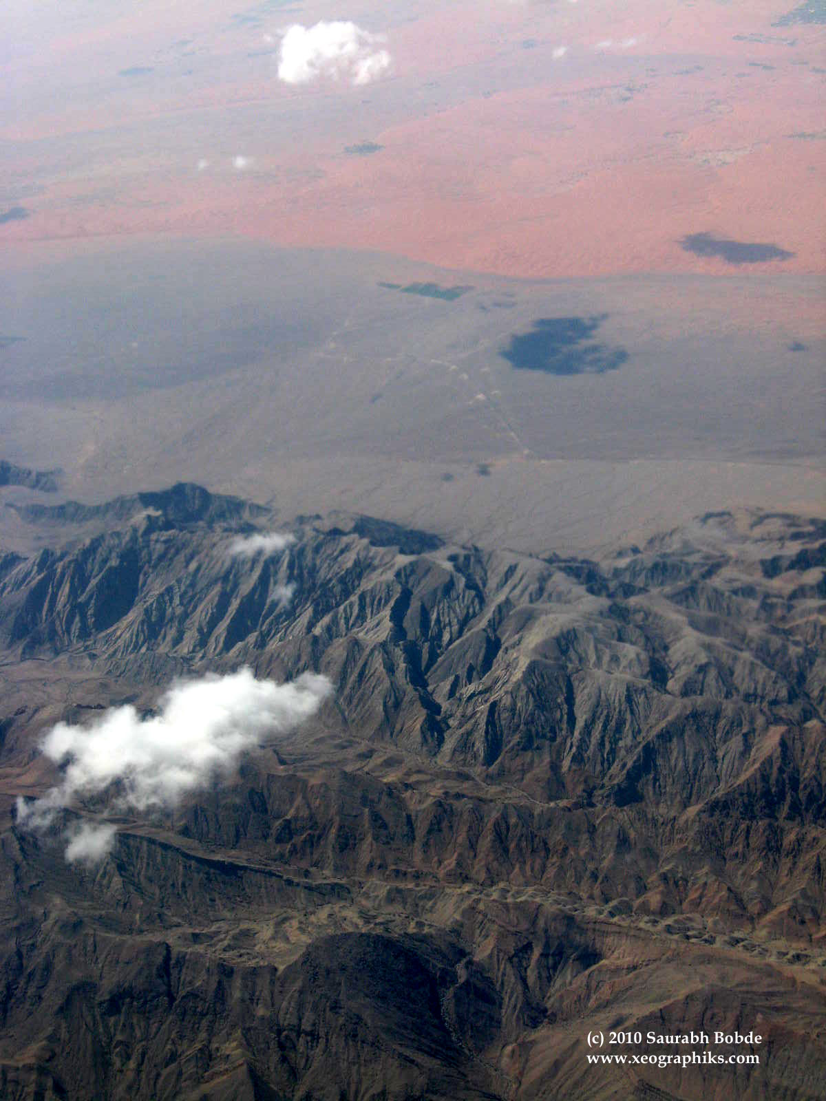 The barren landscape could well resemble that of another planet, like Mars. The white, fluffy cloud floats gracefully against the brown, barren mountains and reddish soil. (Just in case, this is still on Earth!)