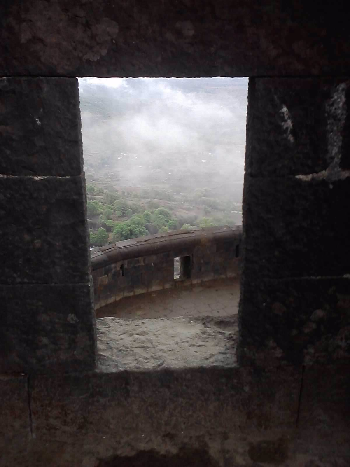 clicked at fort in lonavala, clouds can be seen through window.