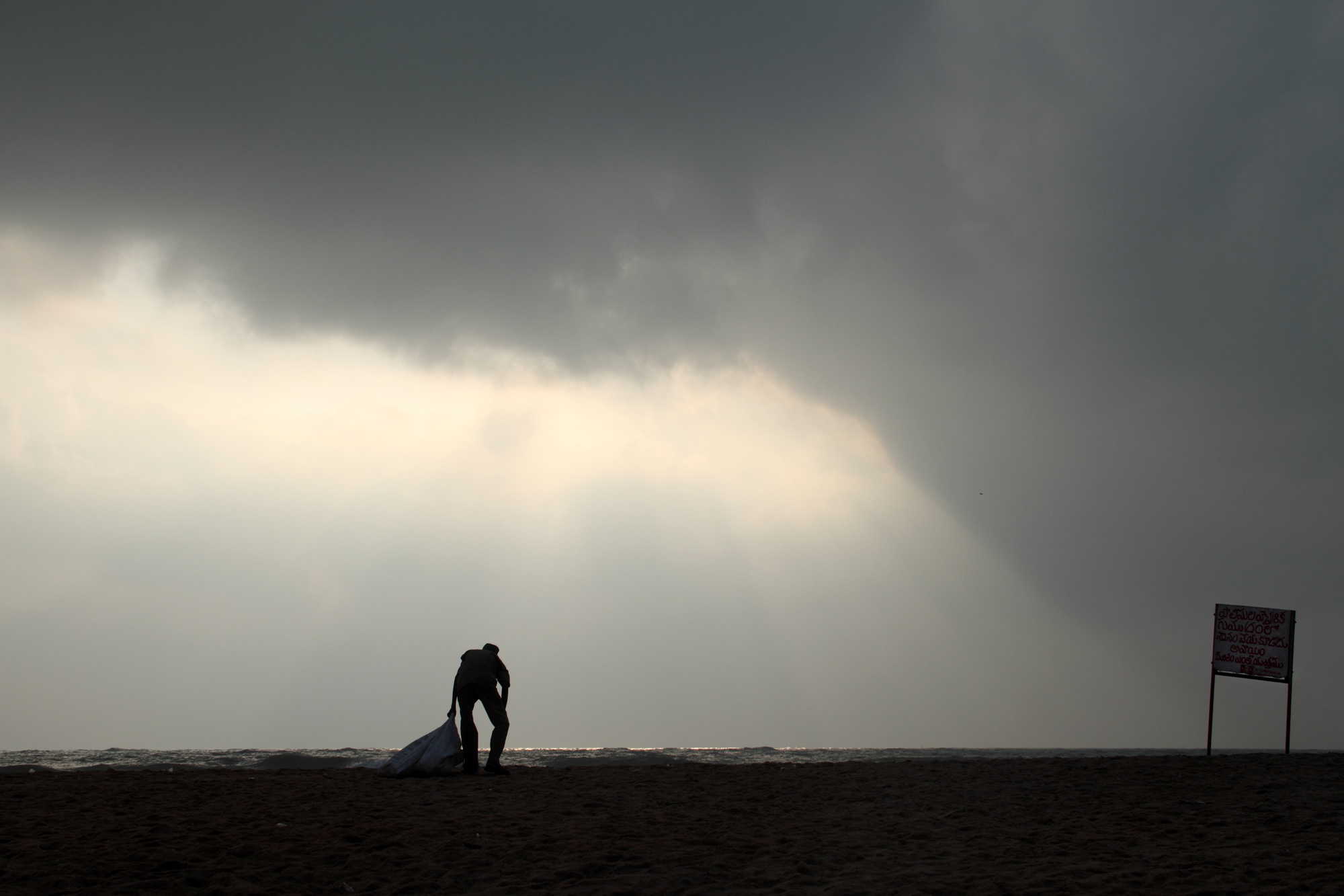 A man cleaning the litter from the Mahabalipuram beach