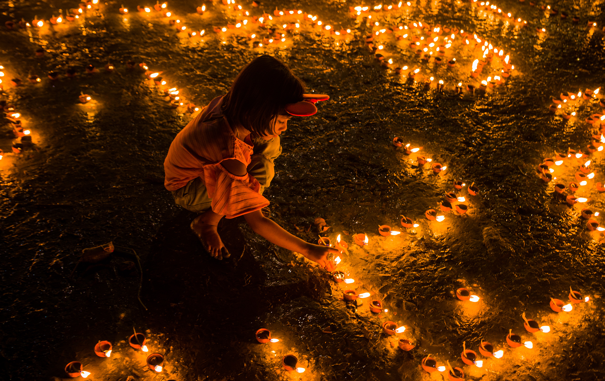 THIS PHOTO BLENDS THE SIDE OF INNOCENCE WITH THE FIRING OF THE DIYA AS A SYMBOL OF ETERNAL ENLIGHTMENT.