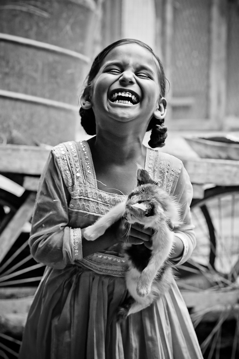 A little girl sharing a funny moment with her pet cat