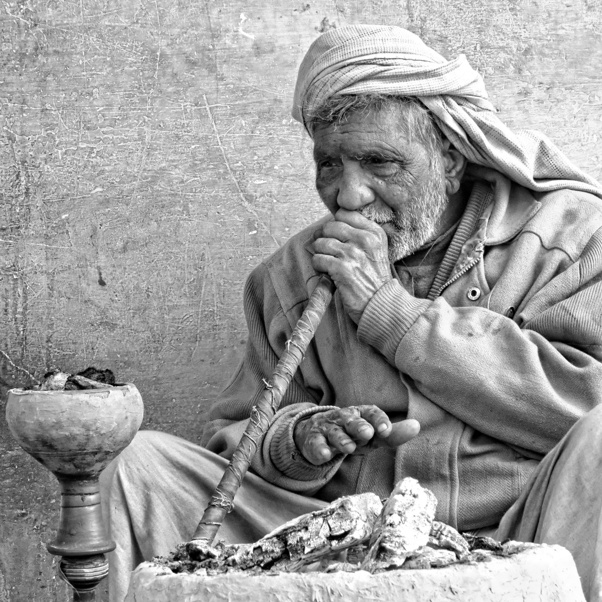 On the cold winter morning the house elder enjoys his hookah while warming his hands on the hot coals