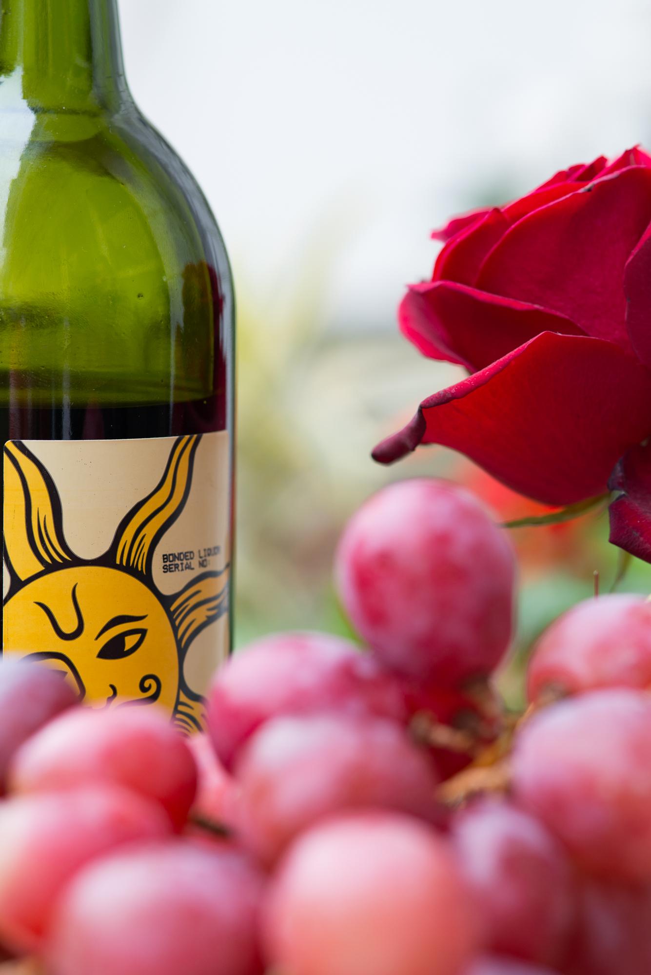 An arrangement of grapes, a wine bottle and a flower.