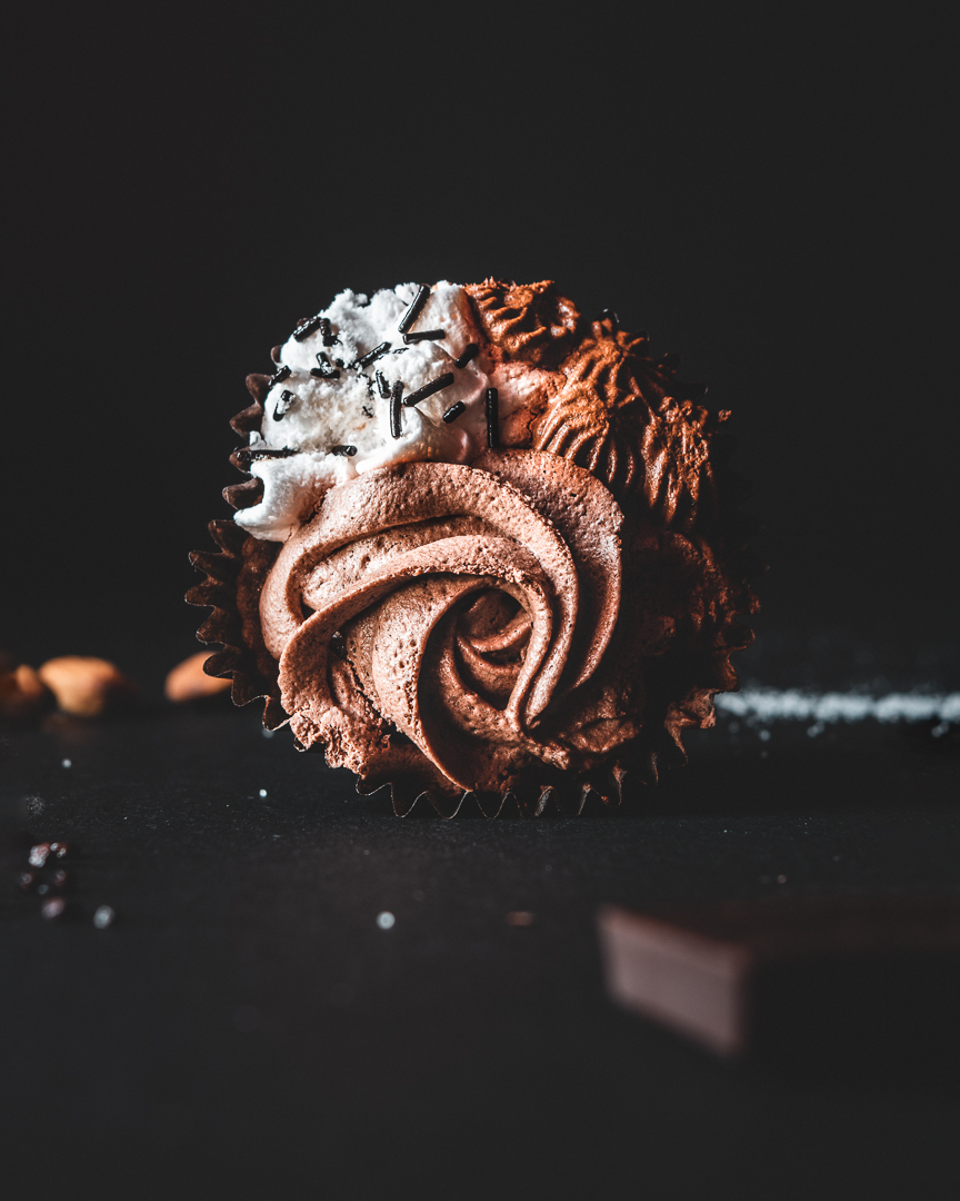 Vertical view of a chocolate cupcake along with its ingredients