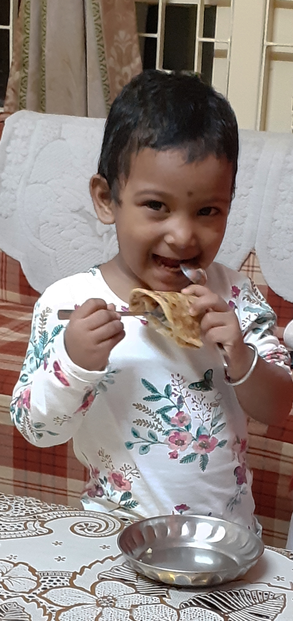 Little baby happy to have a bite into the parantha