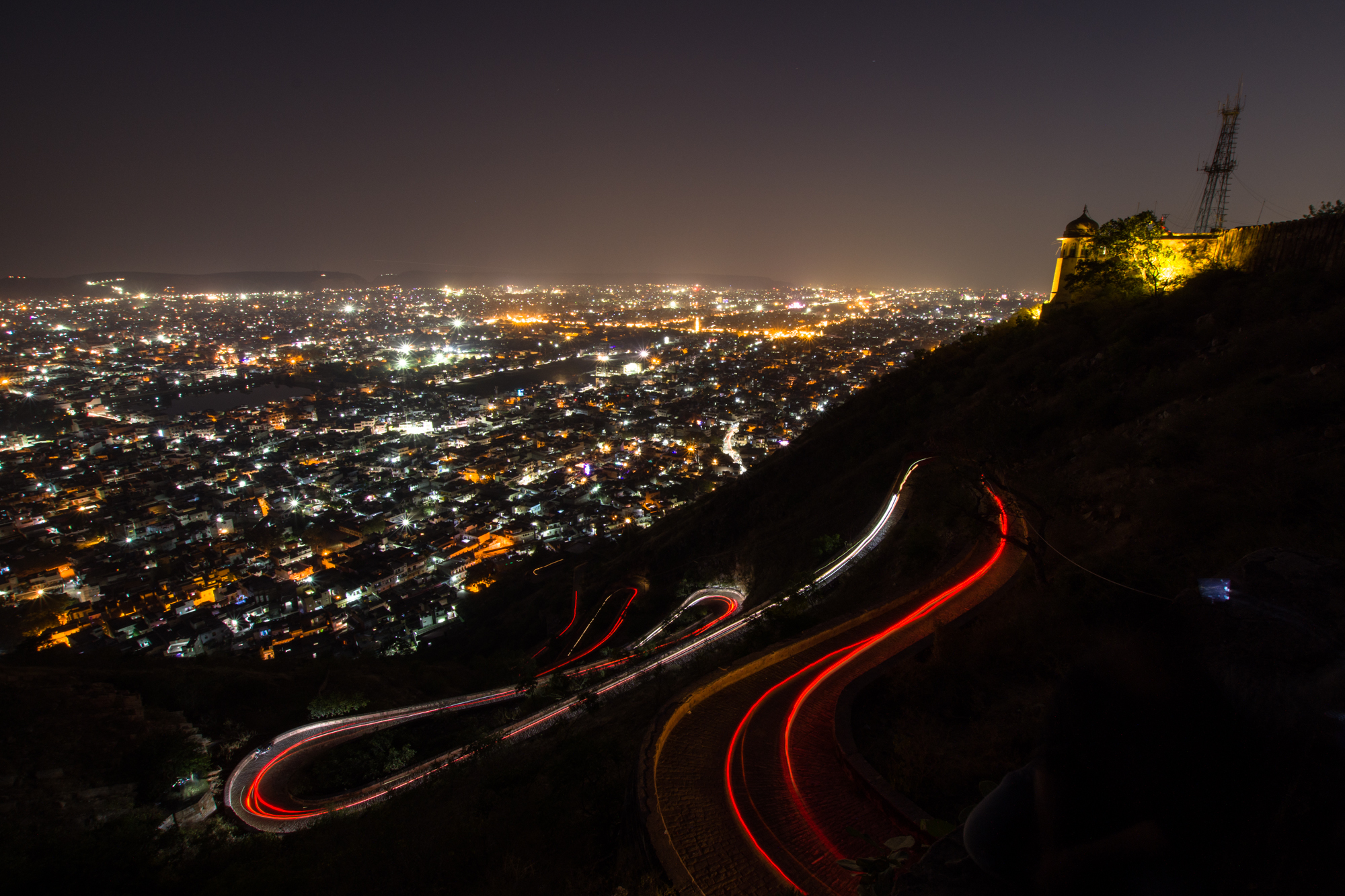 Zigzag root for the vehicles to visit a fort in Jaipur. Photograph taken while people are leaving from the fort. Curvy light trails along with the city lights creating mesmerizing urban pateern.