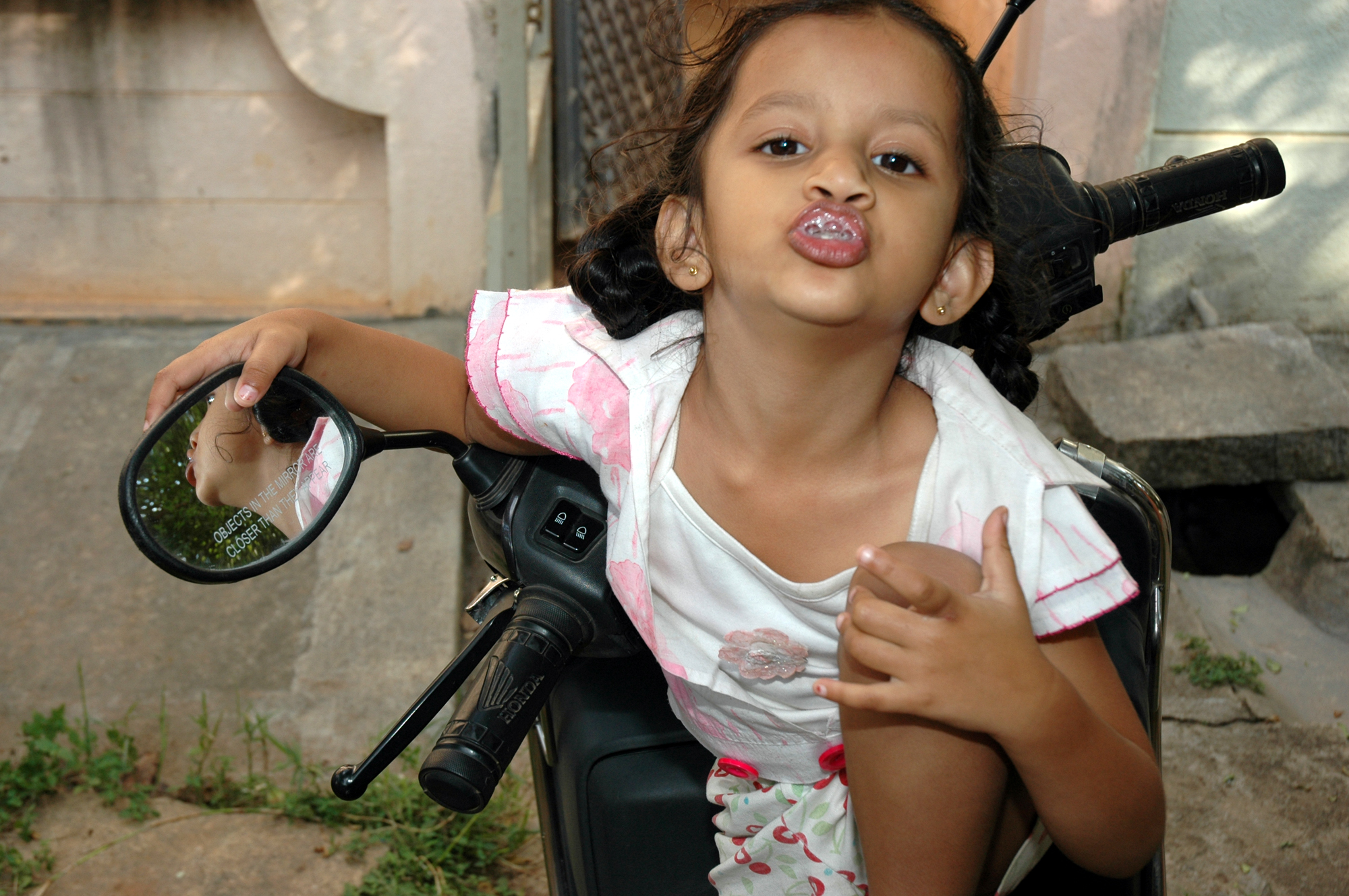 Kid playing reflected in the rear view mirror of the two wheeler on which she is sitting