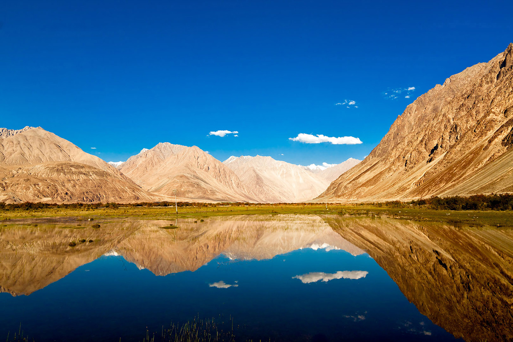 Clear beautiful water reflecting the skies, the blues and the himalayan ranges of Ladakh